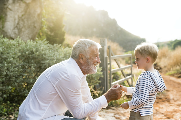 A grandfather shaking hands with his grandson—or perhaps handing something to him