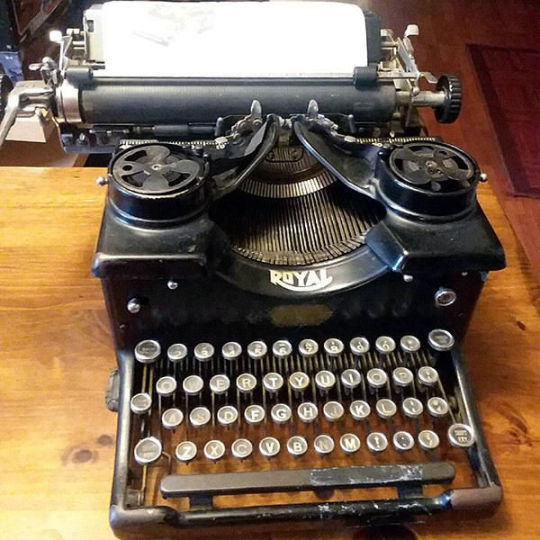 A 1909 Royal antique typewriter with a blank sheet of paper sits on a wooden desk.