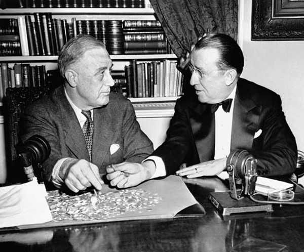 Franklin Delano Roosevelt sits at table covered in dimes with Basil O'Connor from the National Foundation for Infantile Paralysis