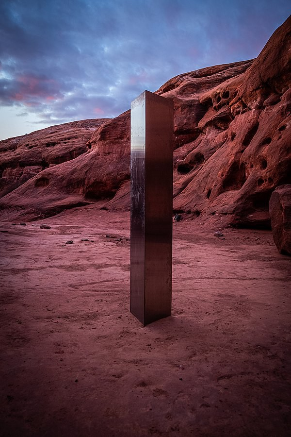 A shiny triangular prism in the red dessert.