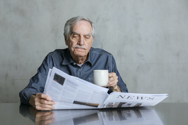 Man reading the newspaper while holding a coffee mug