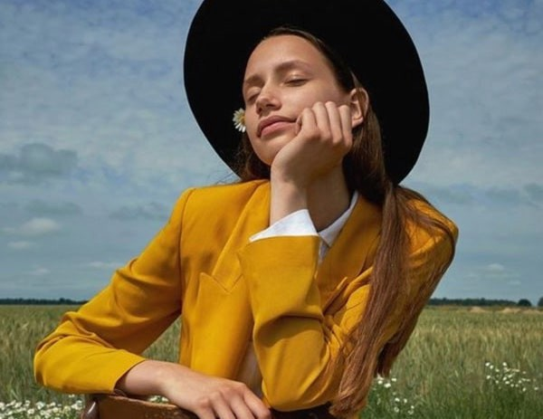 Model poses in mustard yellow suit