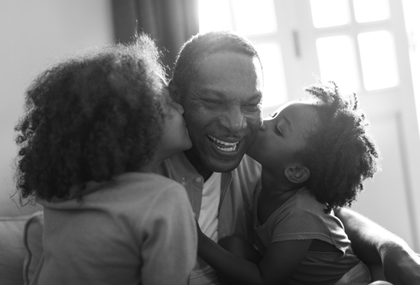 Two children kissing their smiling father