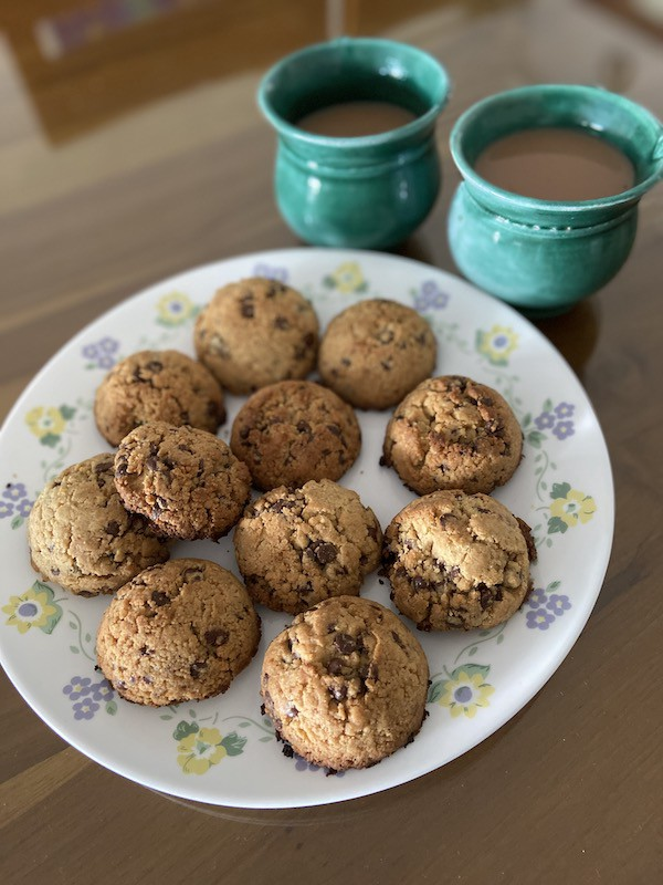 Two cups of tea and a plate of chocolate chip cookies