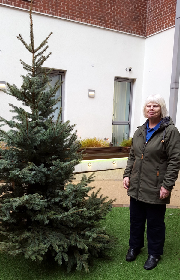 Sylvia Cheetham stood by the new Christmas Tree in the Dementia Garden
