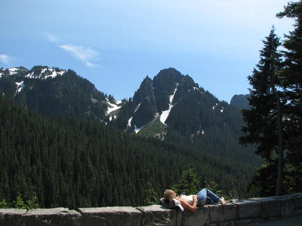 A woman lays on the wall of an overlook in Mt Ranier State Park, mountains, trees, and sky in the background
