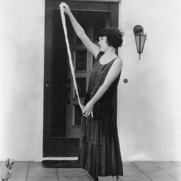 Black and white image of woman holding a long piece of paper