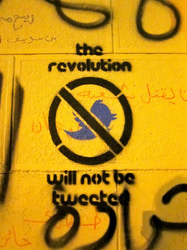 "Street art saying ""the revolution will not be tweeted"" with a Twitter bird with a line through it"