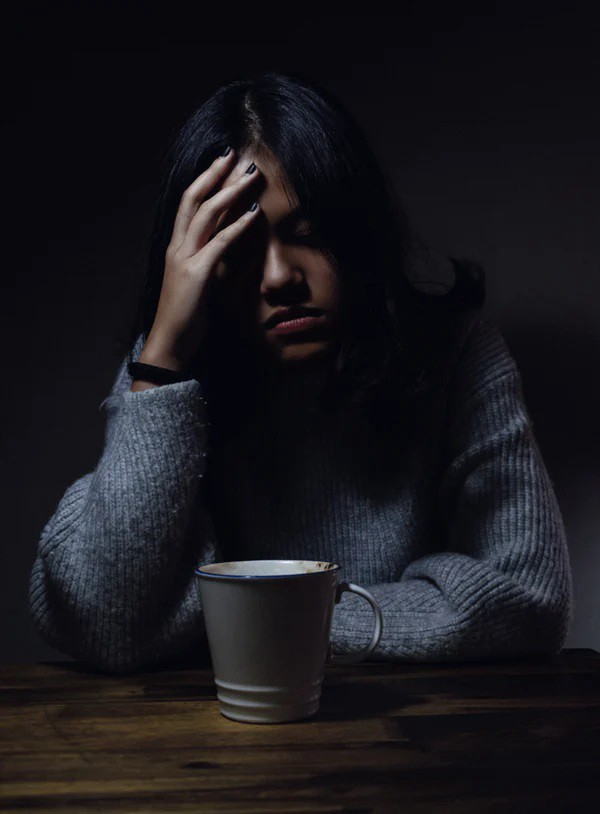 Woman worrying over a cup of coffee, hand on forehead