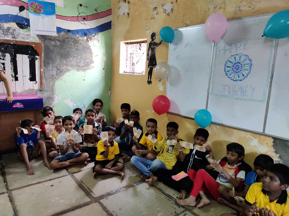 Children sitting inside a classroom holding 10 rupees note for donating