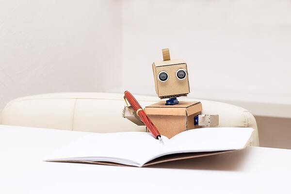 Cute robot writing on paper with a pen
