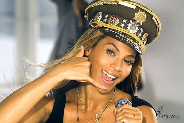 "Beyonce from her ""Love on Top"" music video gesturing a phone with her hand"