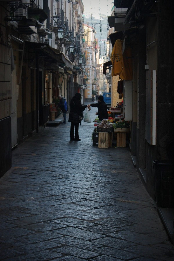 A shop owner hands a customer some produce in a narrow alley at dawn