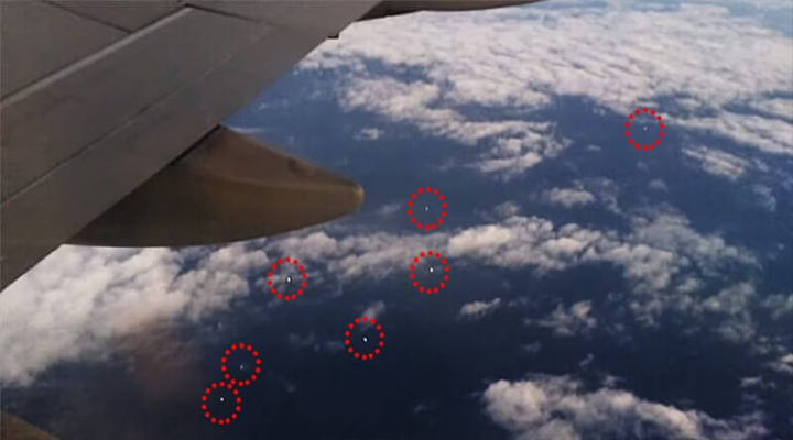 AN ENTIRE FLEET OF UFOS WAS FILMED WHILE FLYING BELOW A JET PLANE