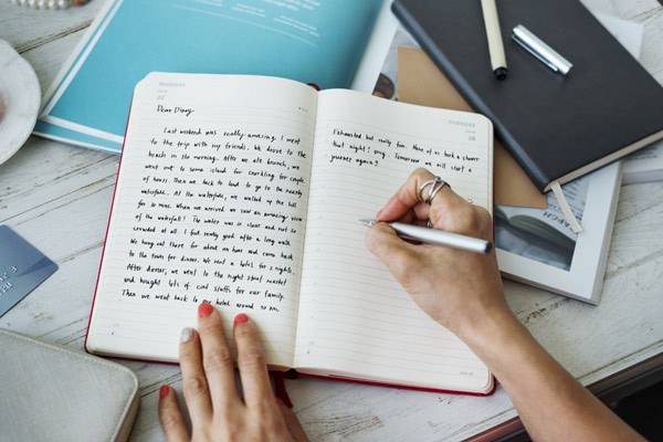Woman holding pen writing on lined pages of a journal.