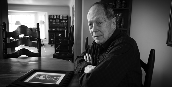 Barry King sits in his dining room with a photograph of his son, Timothy King. Photo courtesy of ABA Journal.