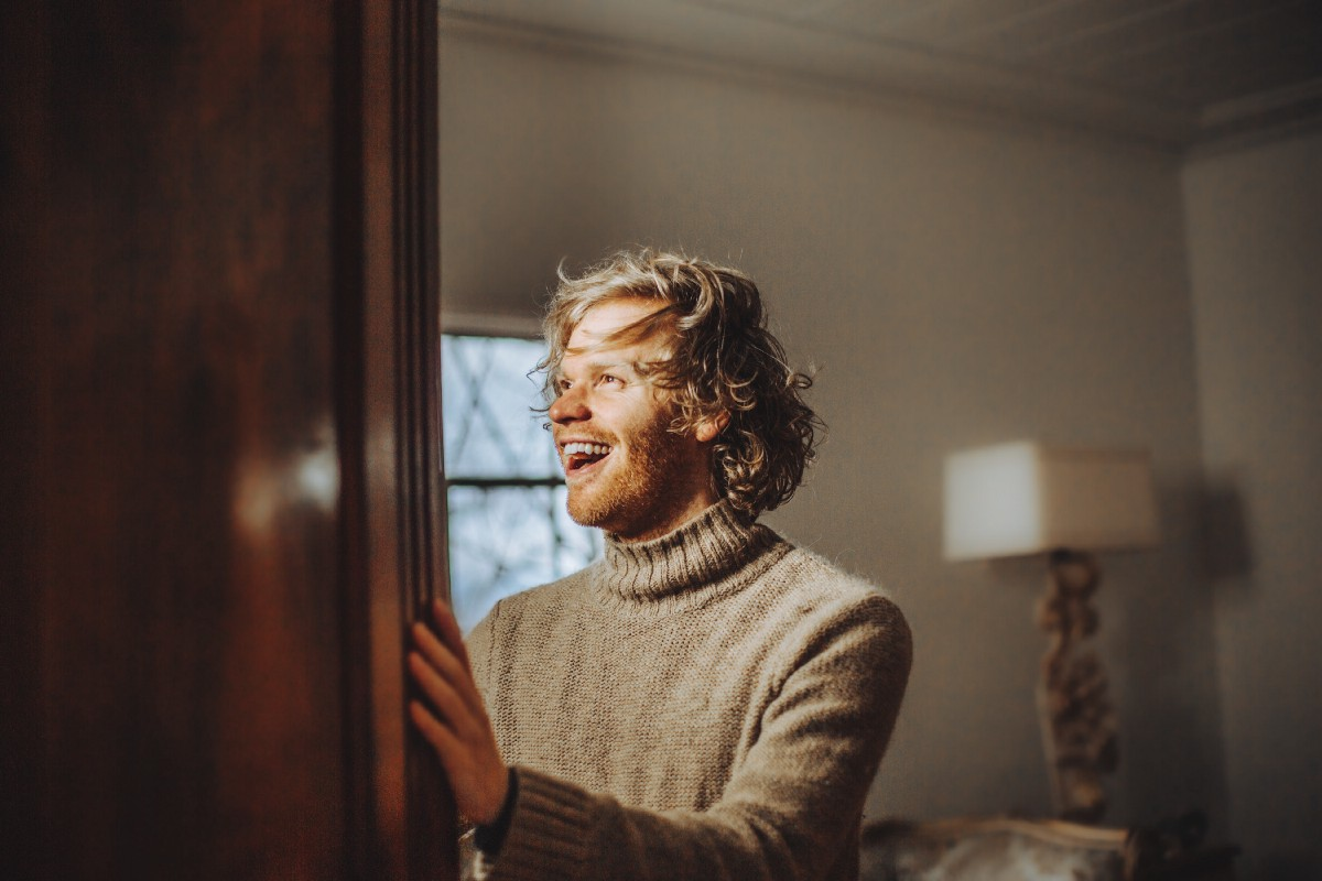 man looking out of door to change