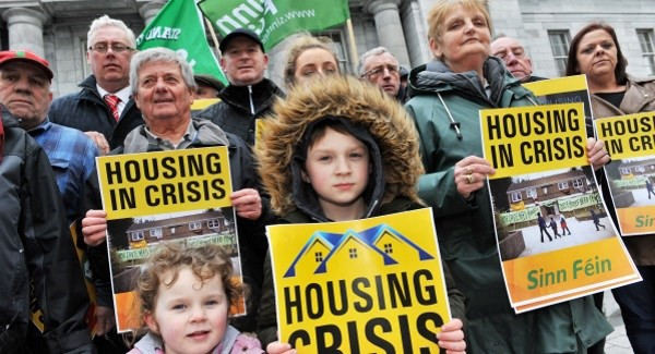 "Sinn Féin activists and politicians holding up signs that say ""Housing in Crisis"" and ""Housing Crisis"""