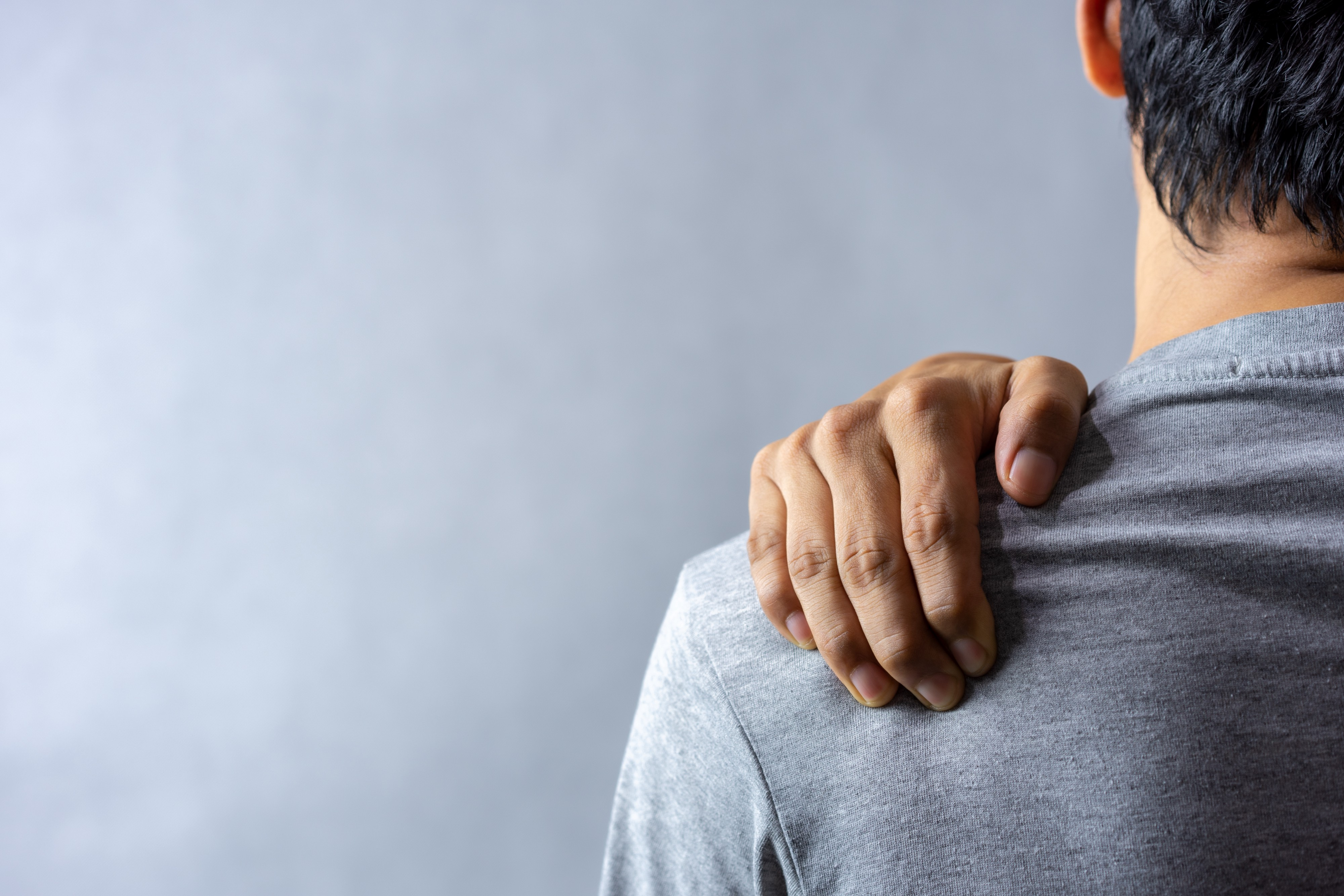 A person holding their left shoulder indicating that it is paining. Stress leads to aches and pains