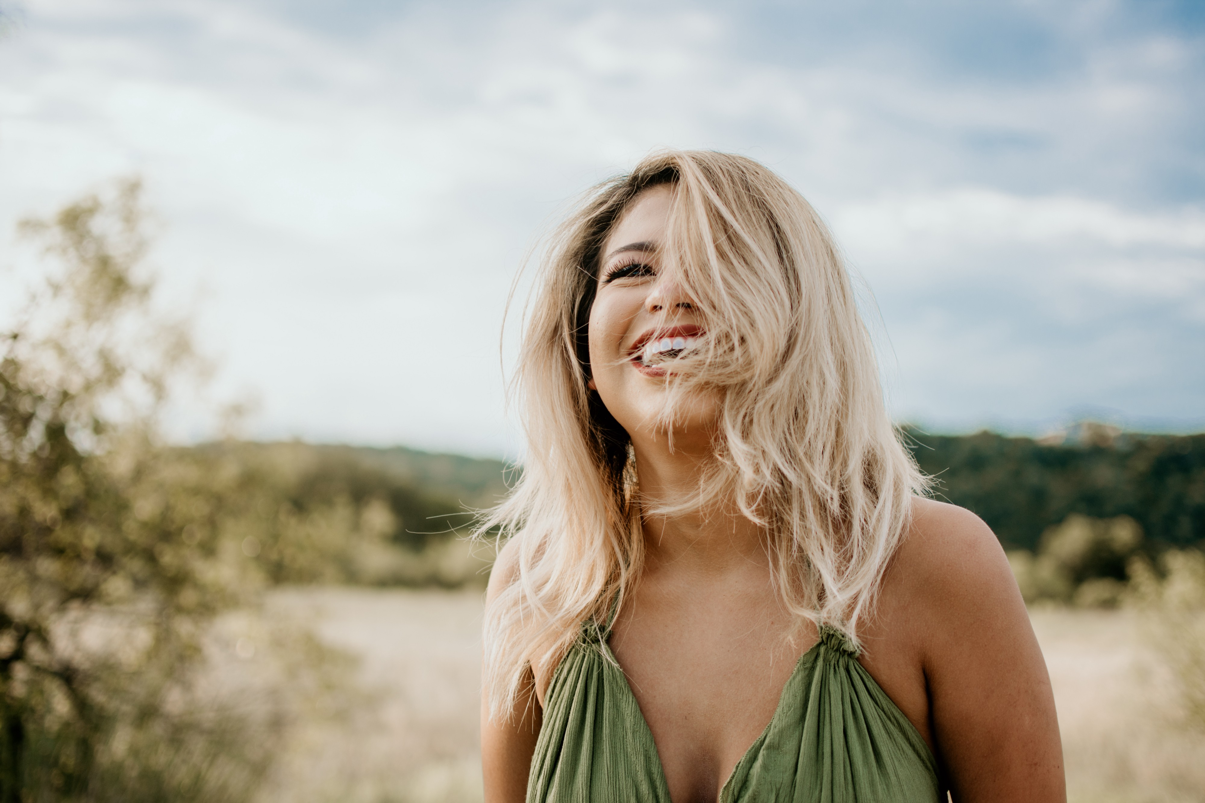 blonde woman laughing on the beach
