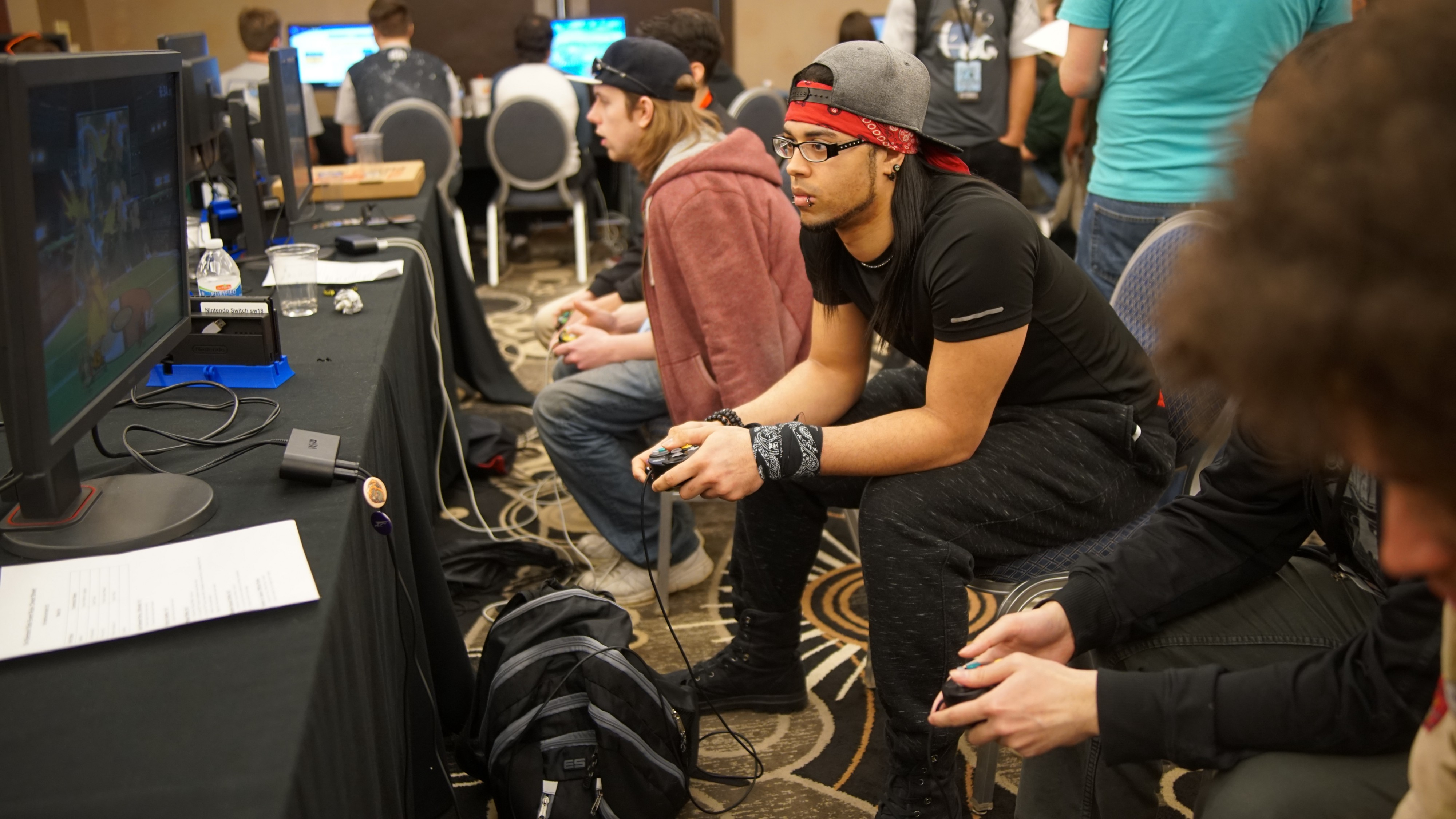 a group of young males sitting together, playing videogames at some sort of convention