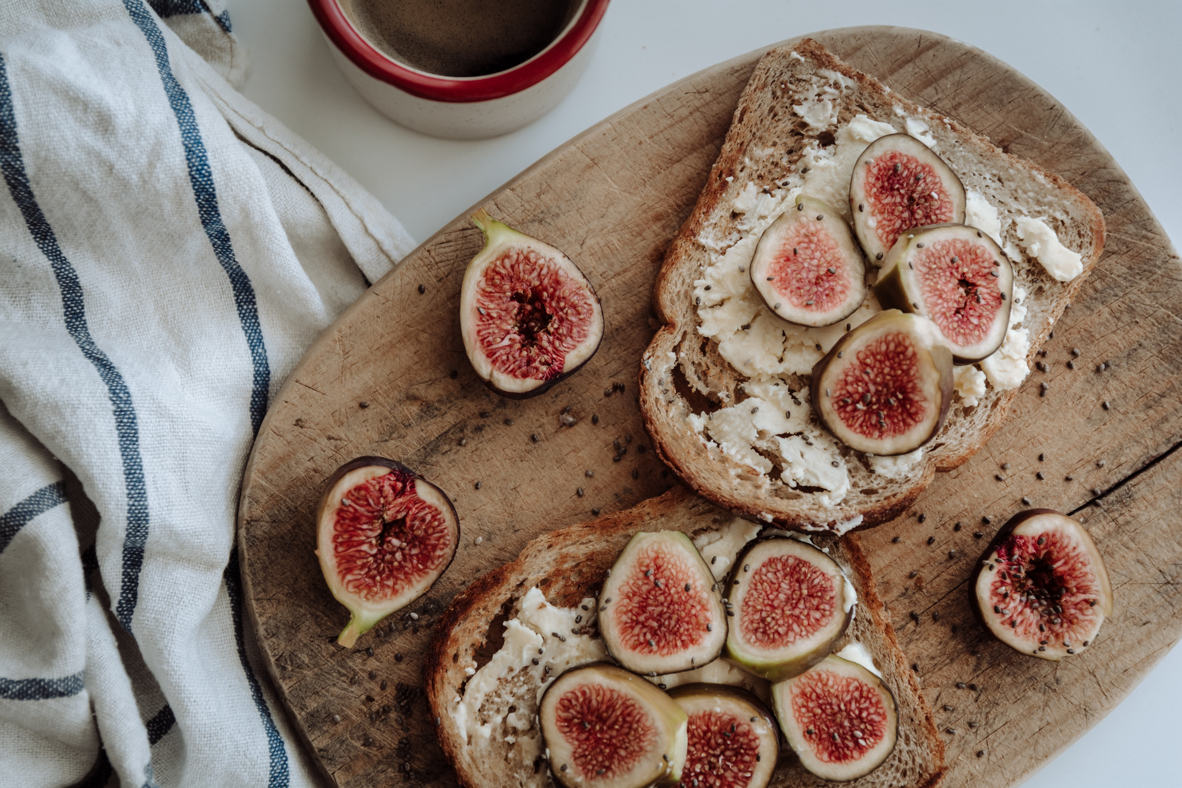 A bright scene of halved figs on thick-cut bread atop a wooden serving board, coffee cup and linen towel casually placed along side.