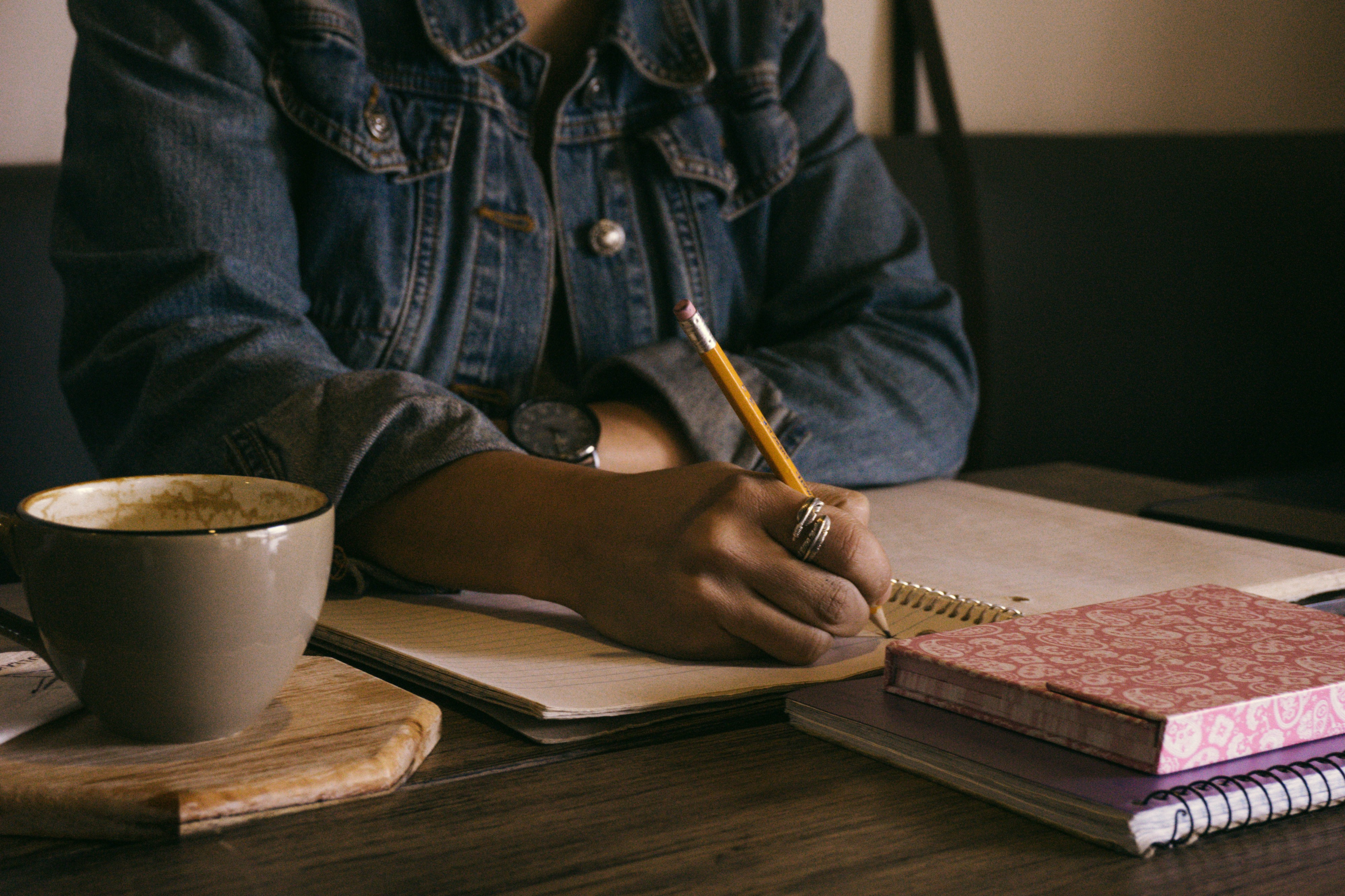 Brown skinned black woman in denim jacket writing in notebook with a pencil. A cup of coffee and two books rest on the table.