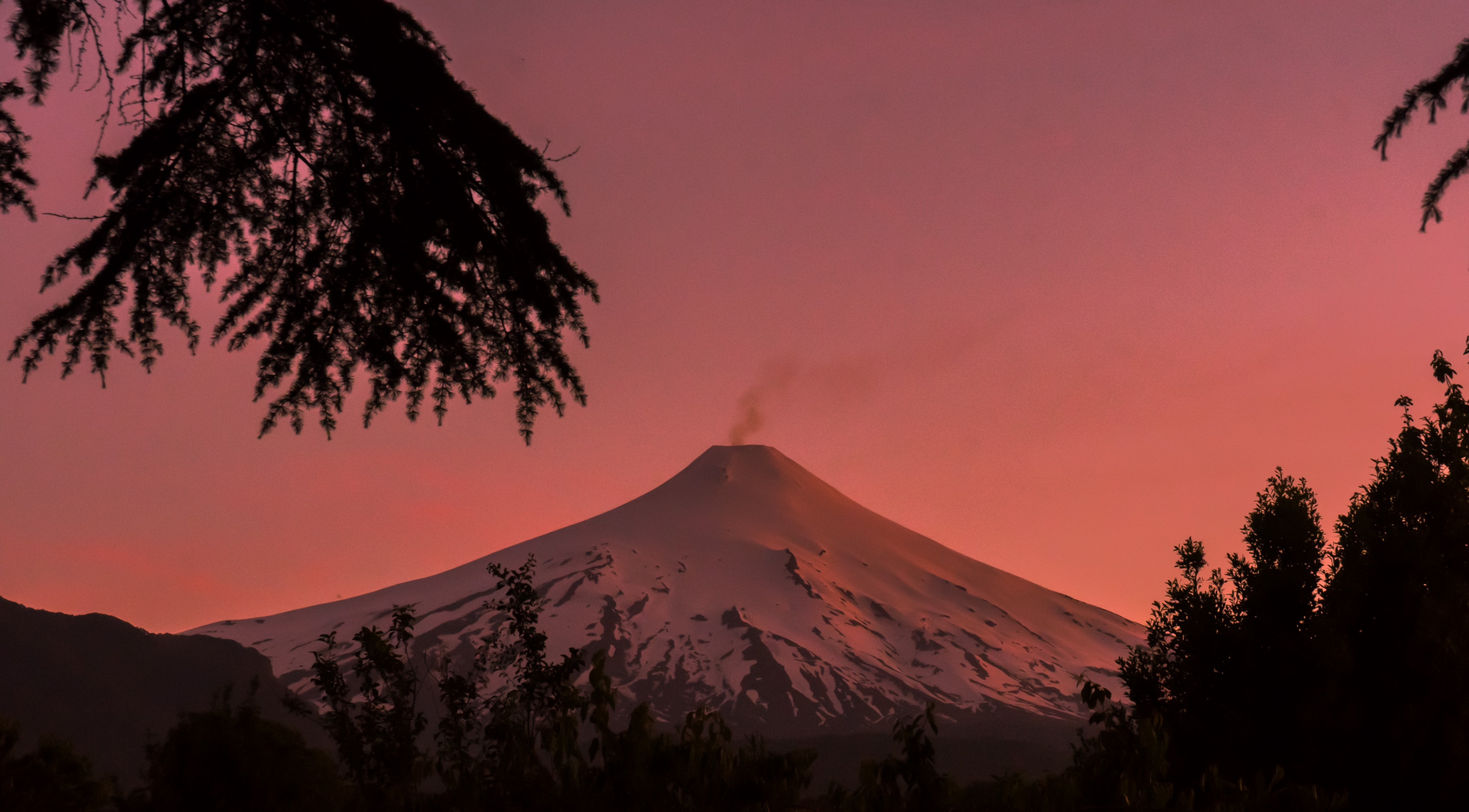 A snowy volcano smoking slightly in the orange of a sunset (or sunrise).