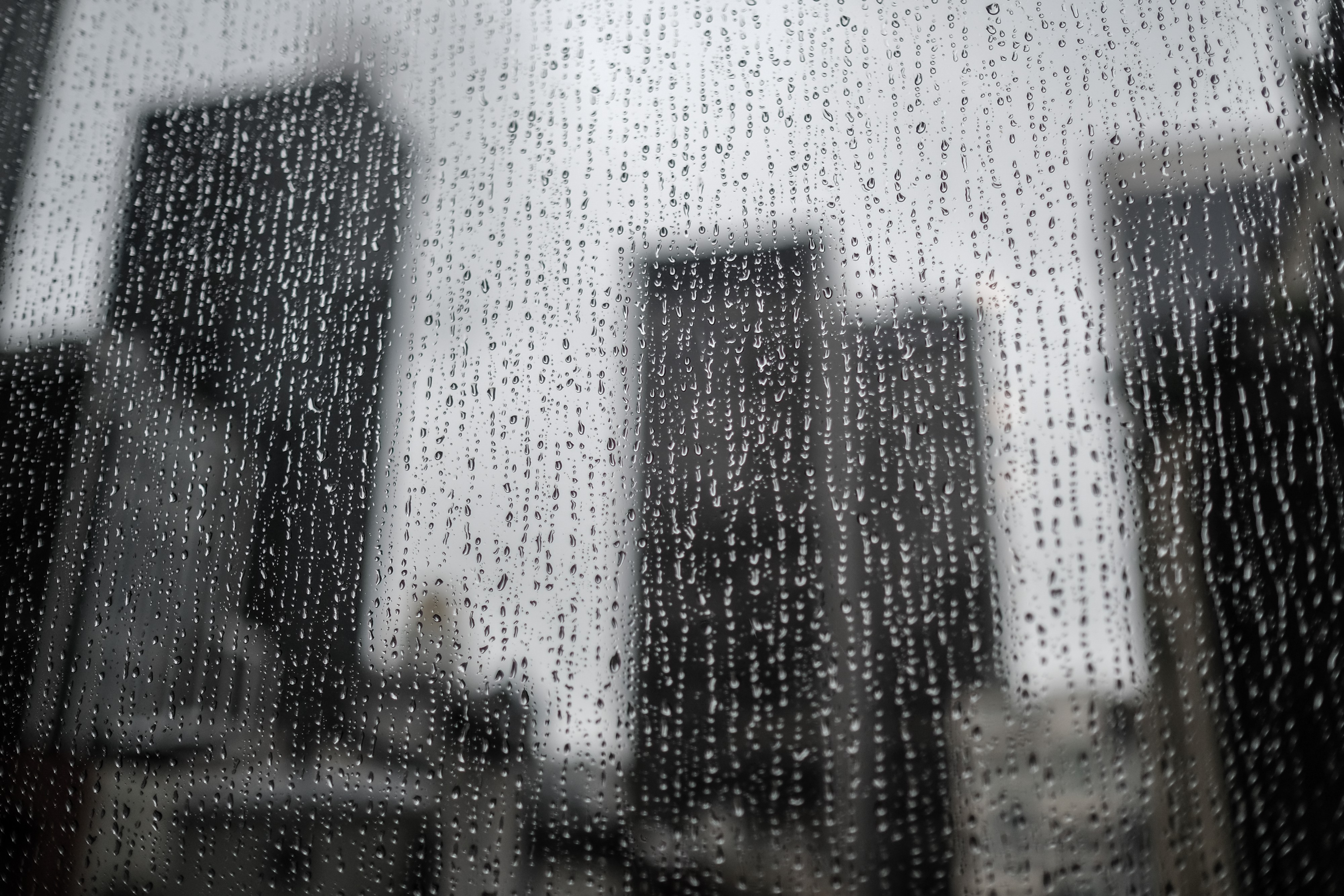 Photo looking out through a window covered with rain drops. There are blurry skyscrapers in the background.