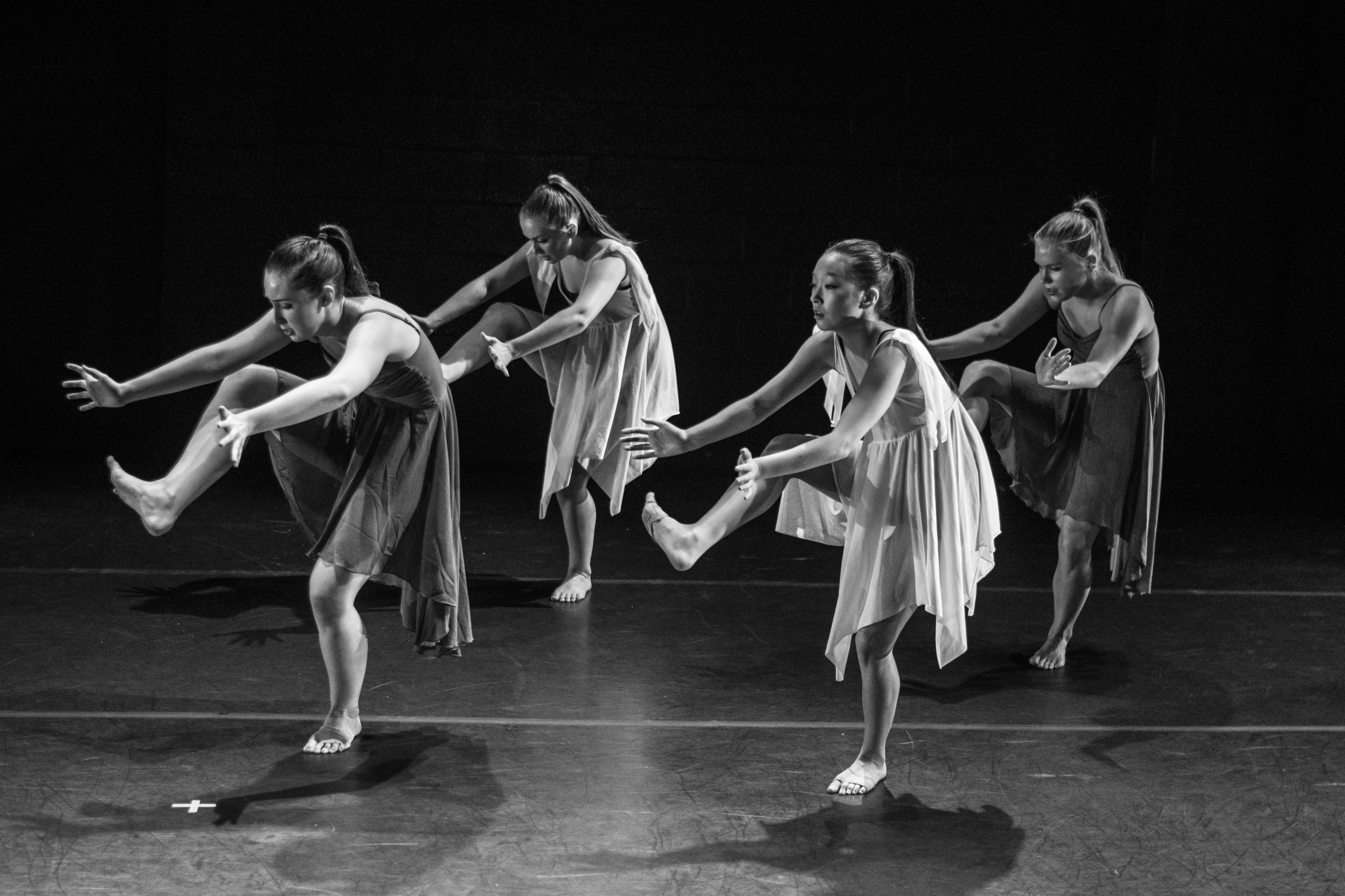 Black and white picture of dancers performing weird dance moves on a stage.