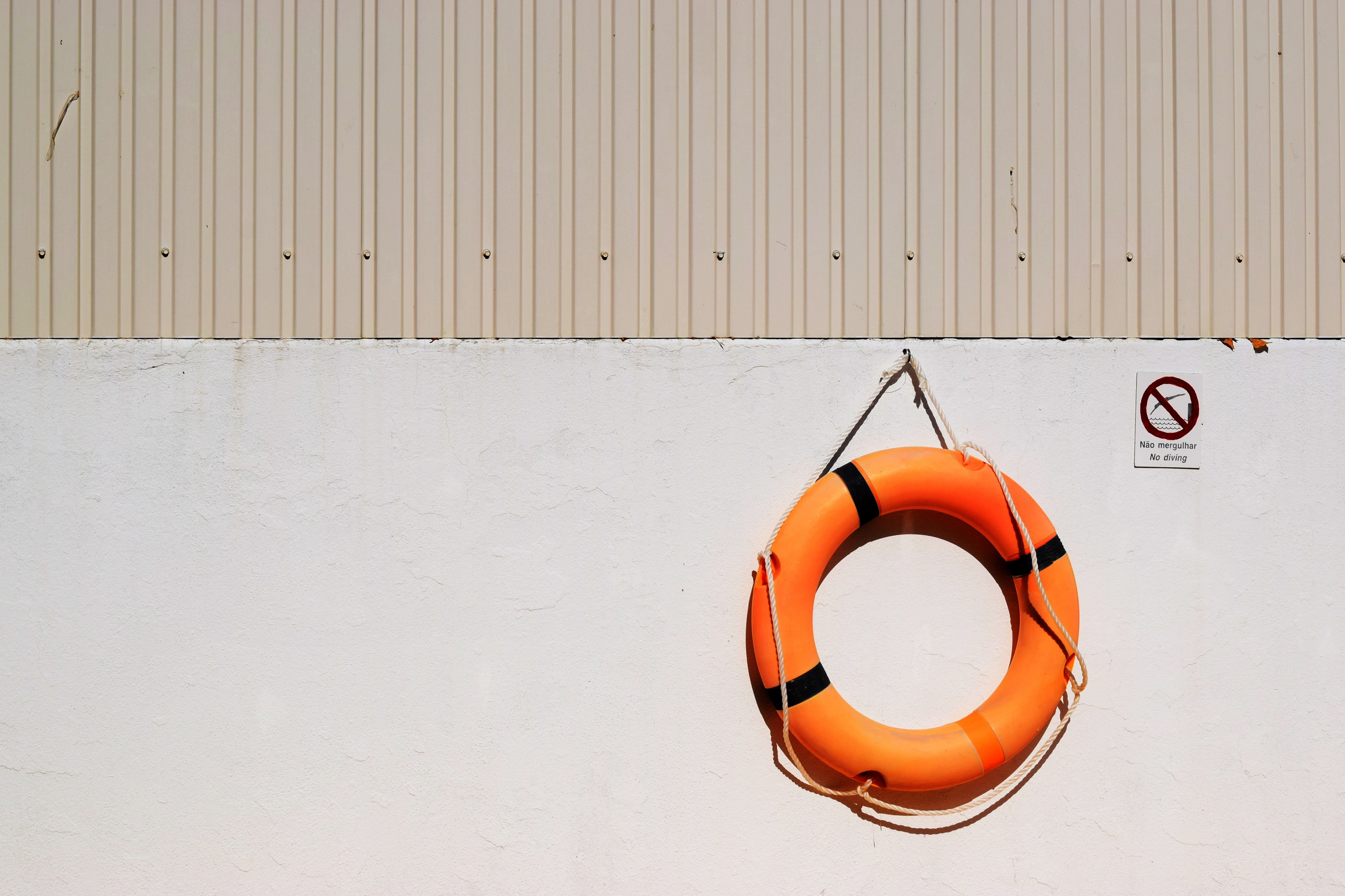"A pool lifesaver hangs on a wall next to a ""No Diving"" sign."