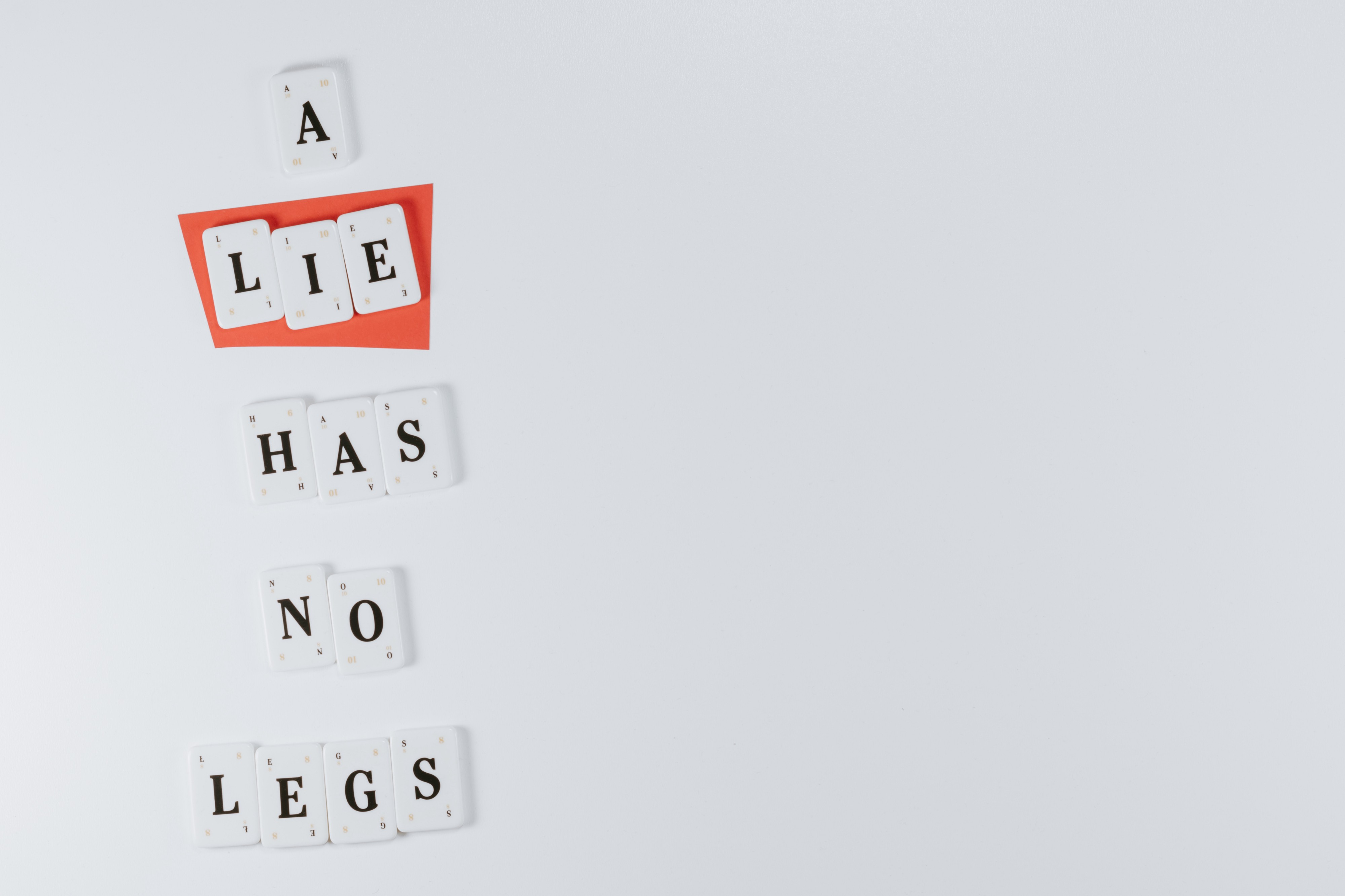 """Scrabble-like tiles that spell out, """"A Lie Has No Legs."""""""