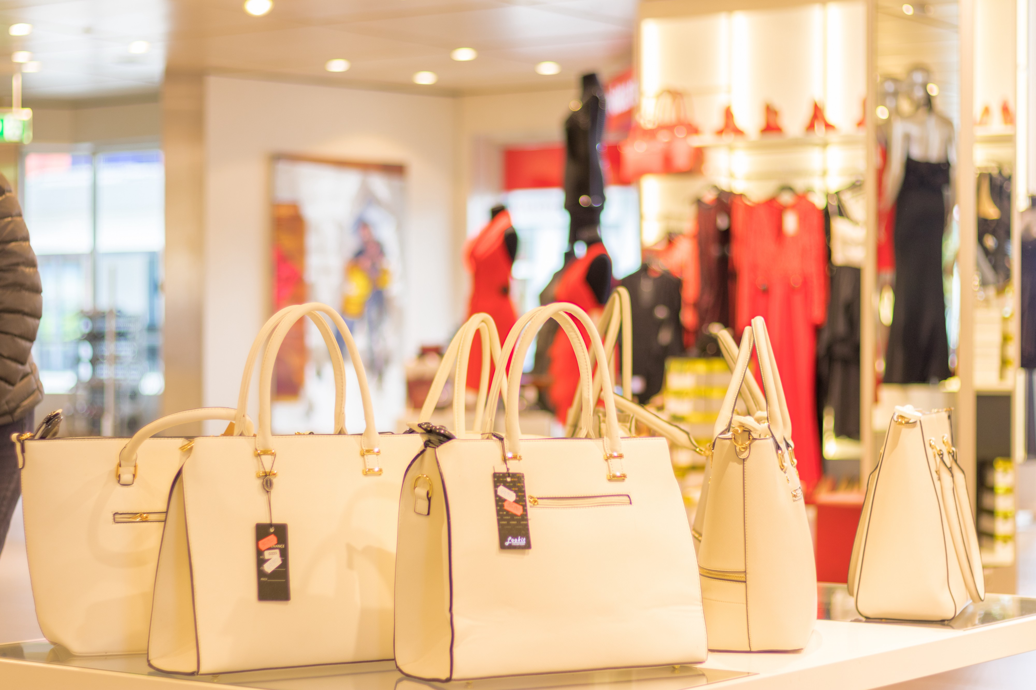 Display of off-white handbags in what looks like a department store