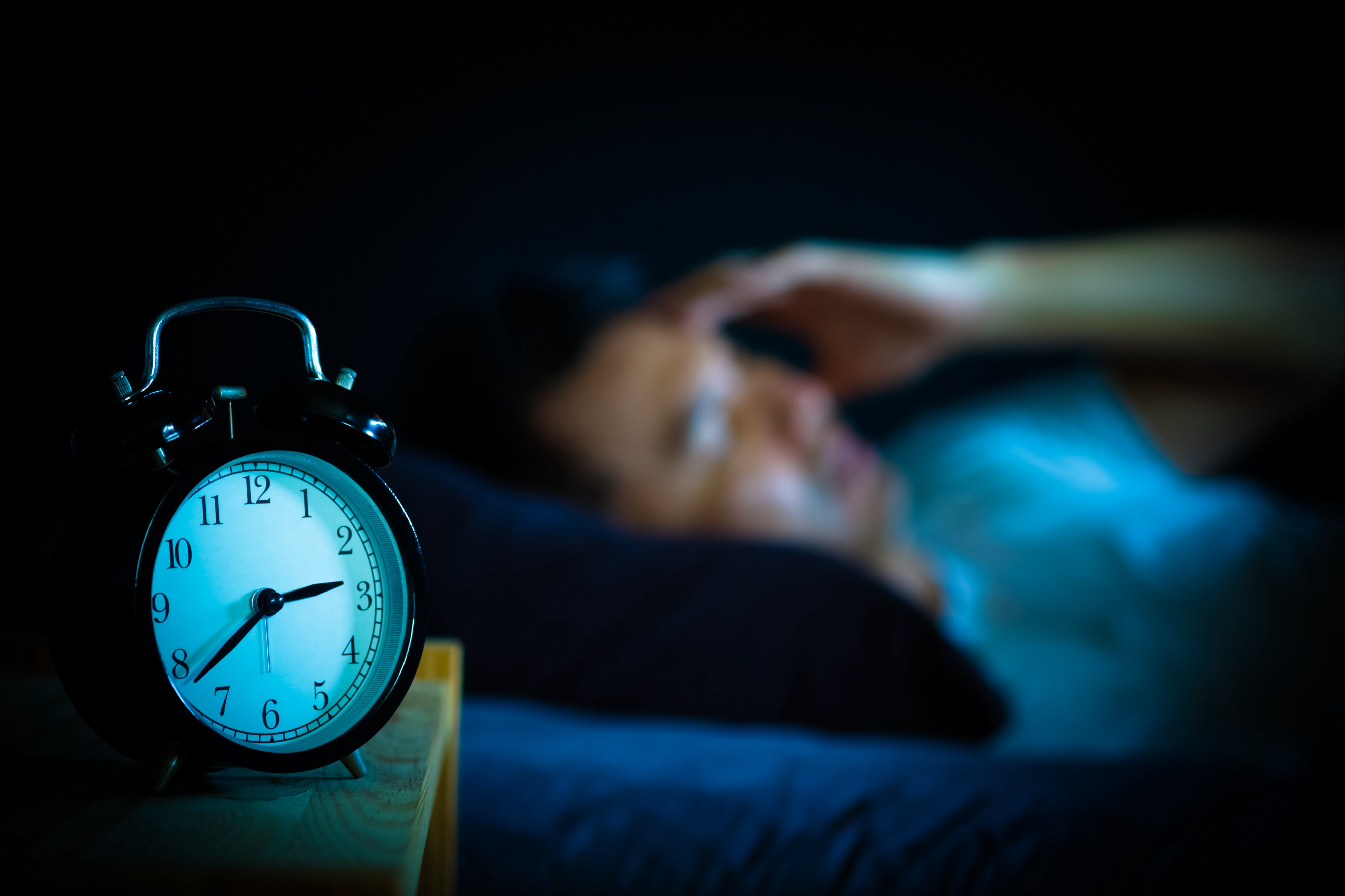 Man in bed suffering insomnia and sleep disorder thinking about his problem at night