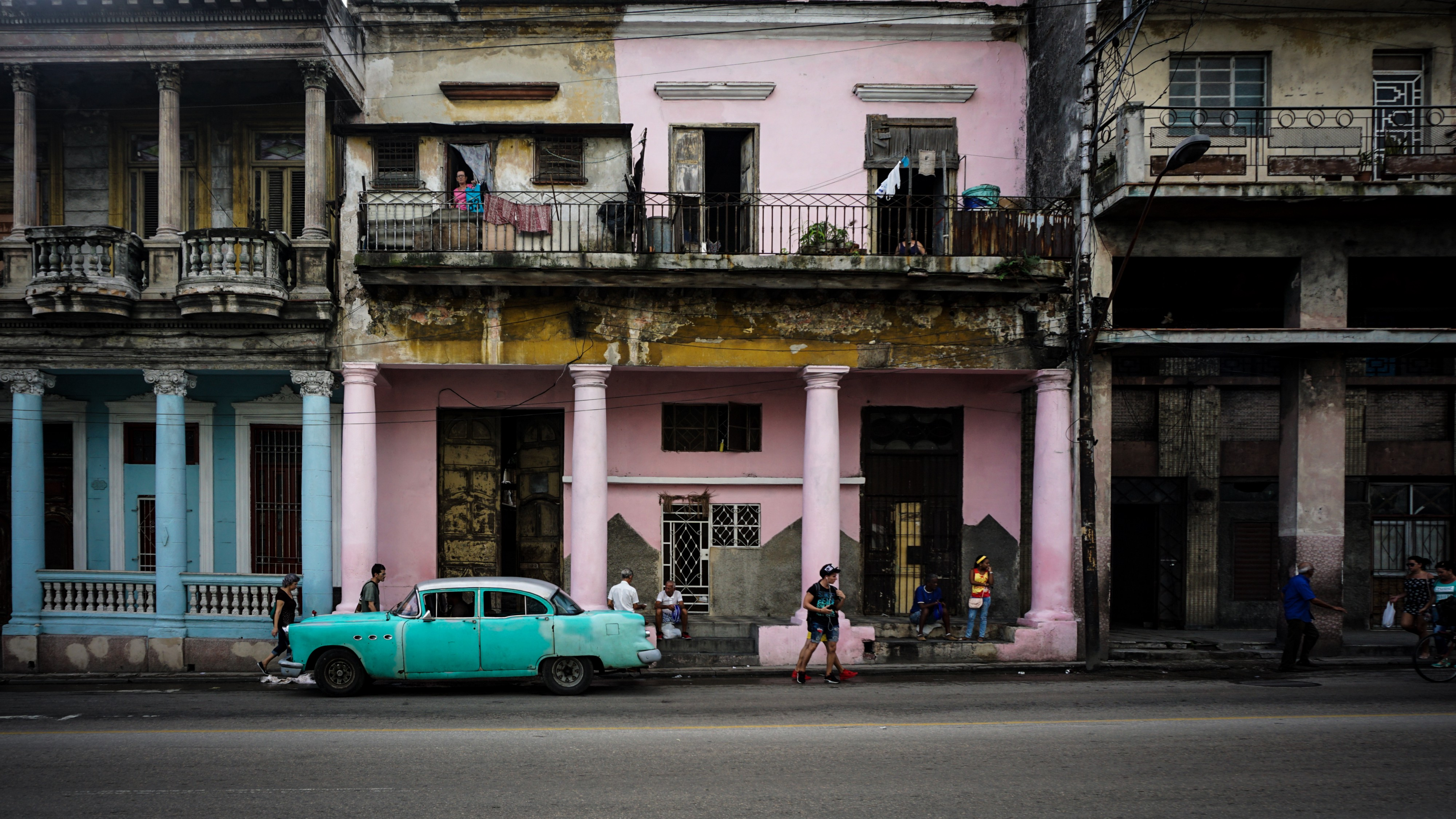 A Caribbean street with colourful houses and an old car parked on the road.