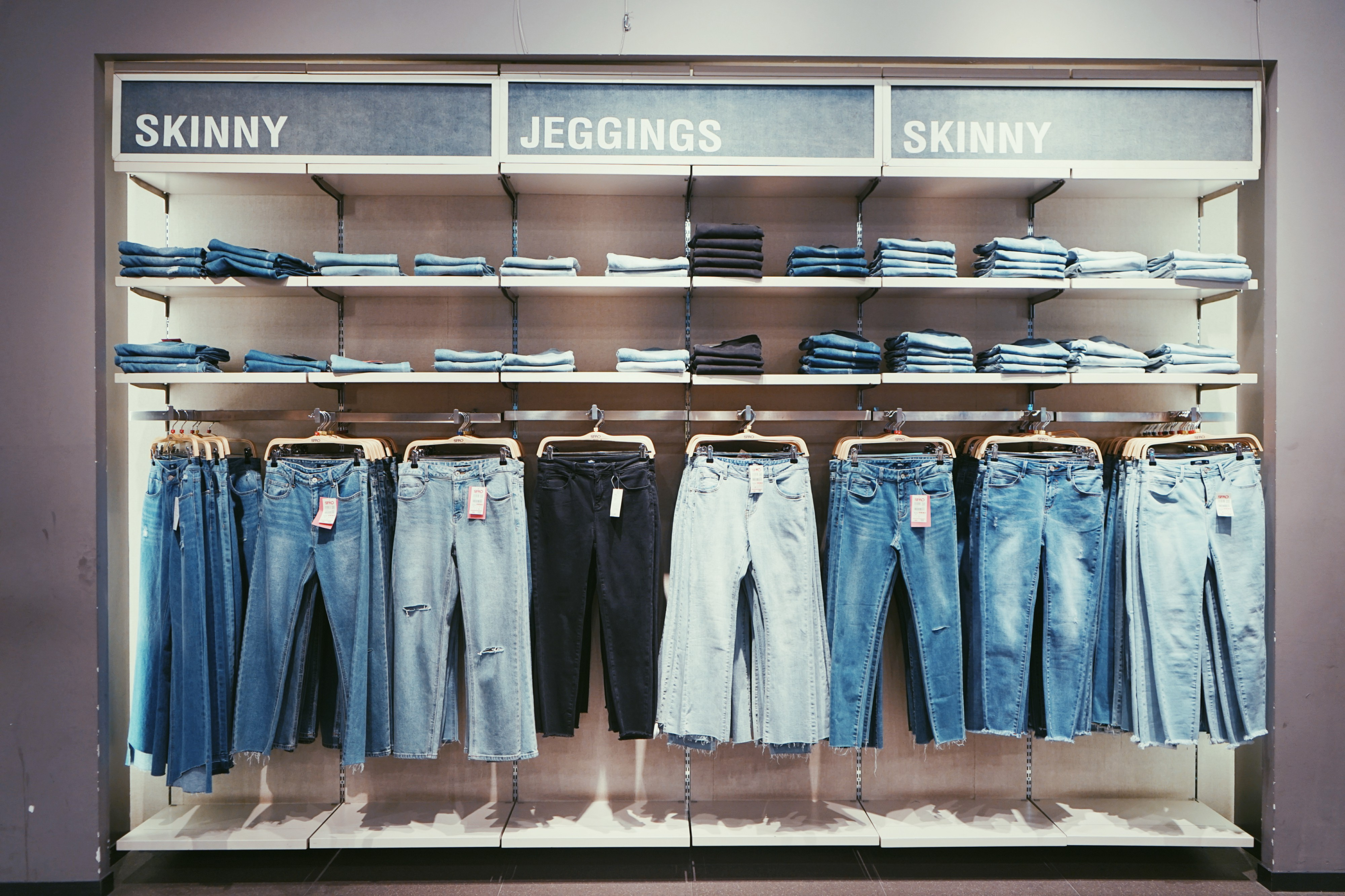 Many jeans hanging in a store