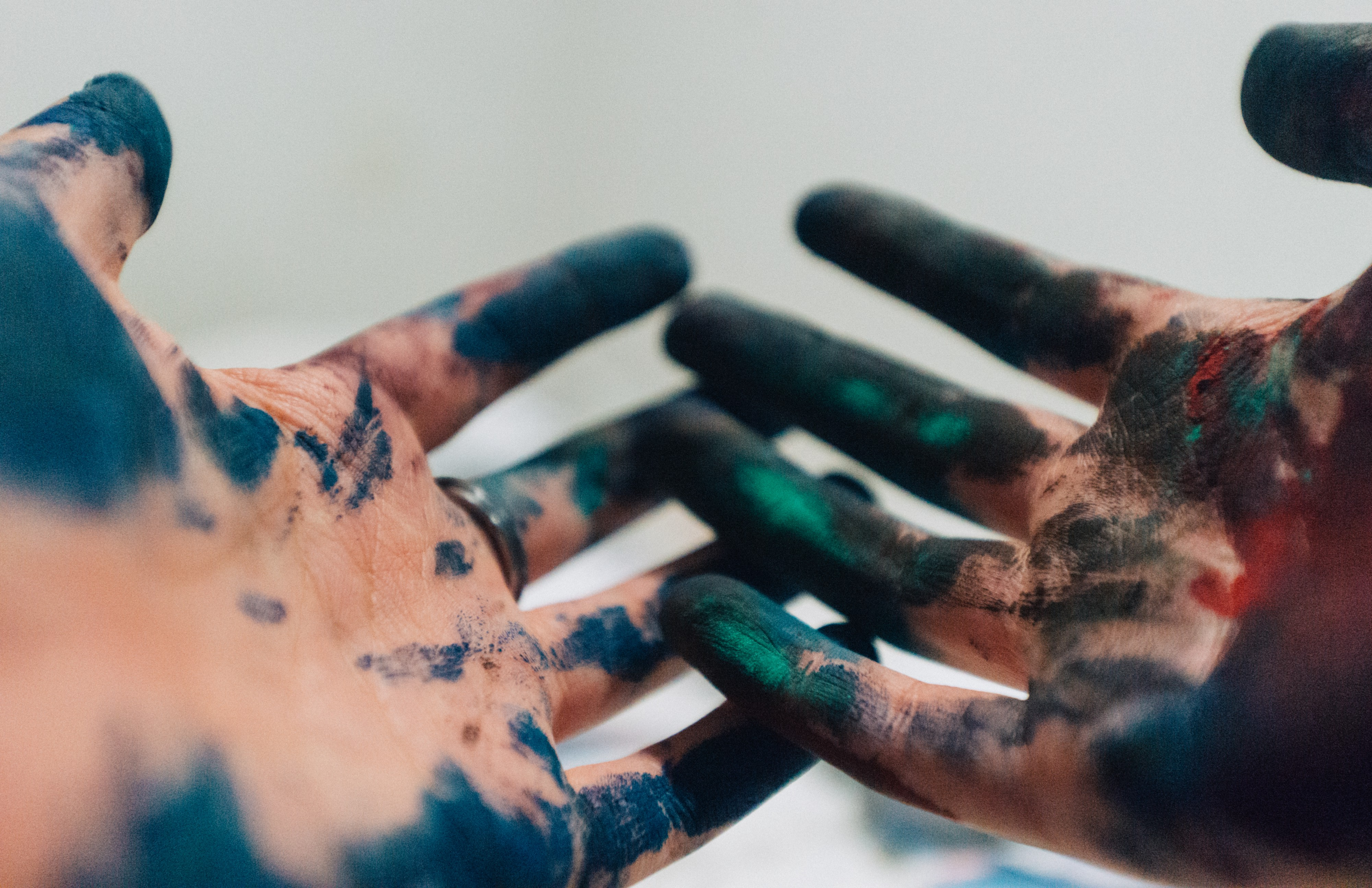 Two hands, palms up, covered in dark blue, black, and green pigments.