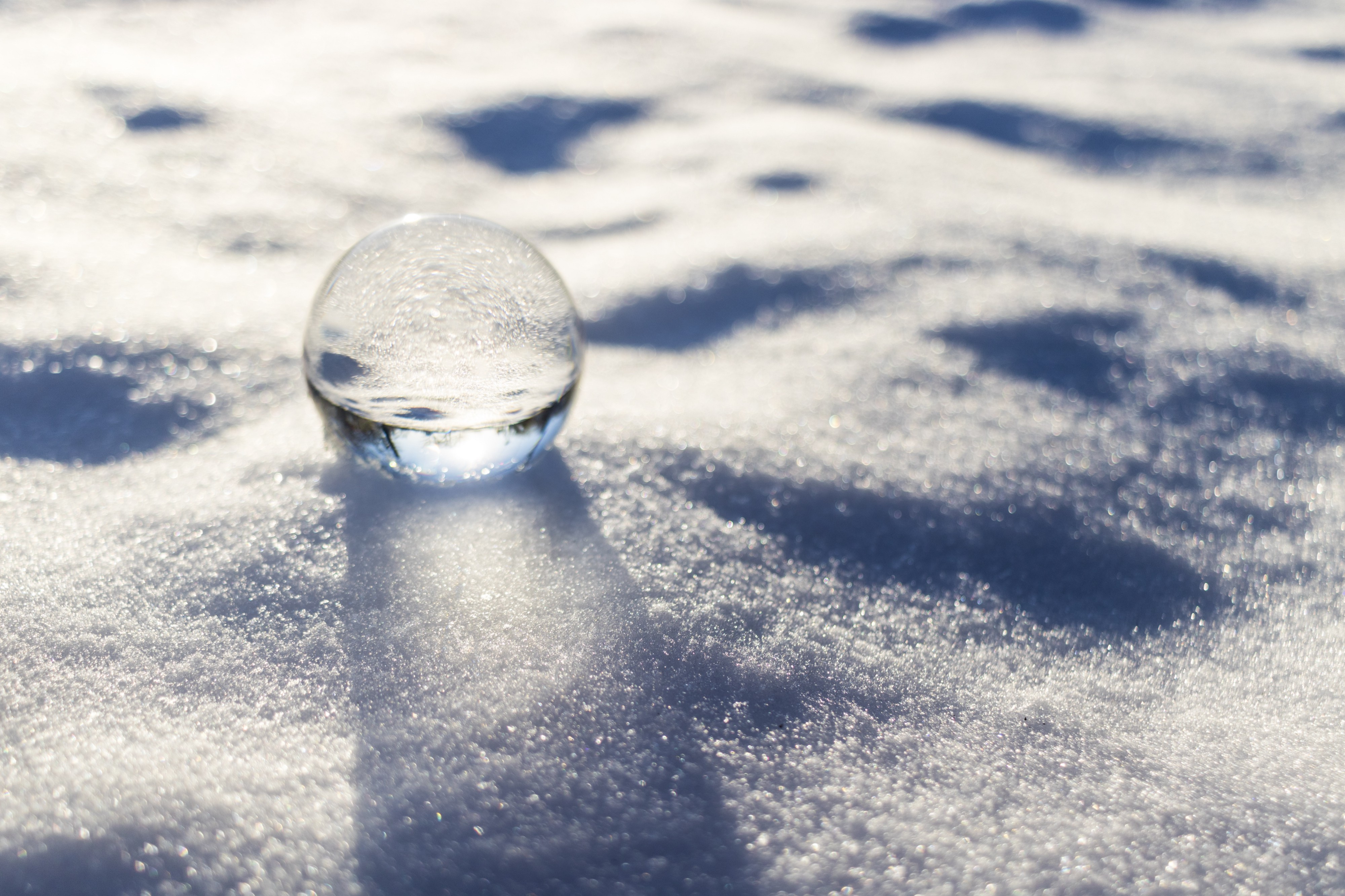 A glass or ice ball sits on a blanket of snow.