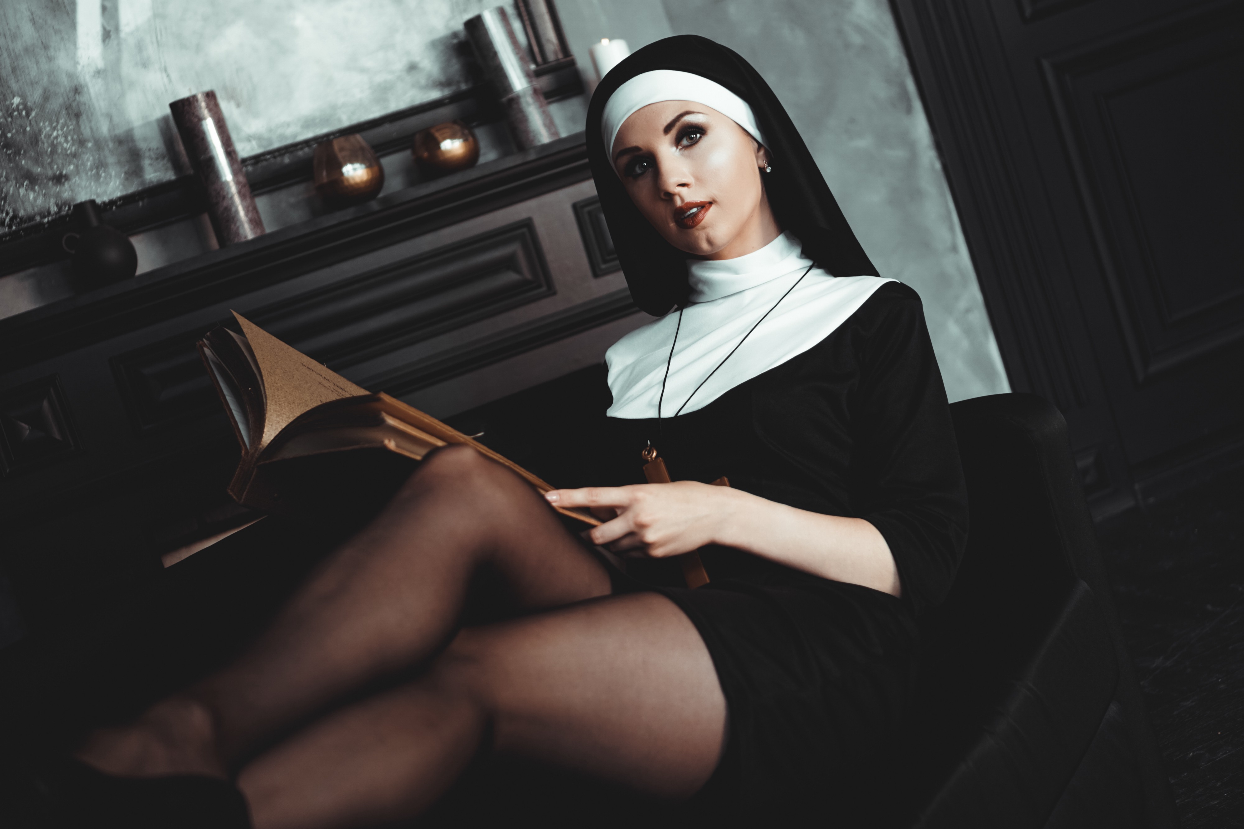 Attractive woman in nun's clothing and black tights, reading a book, lying back on a couch.