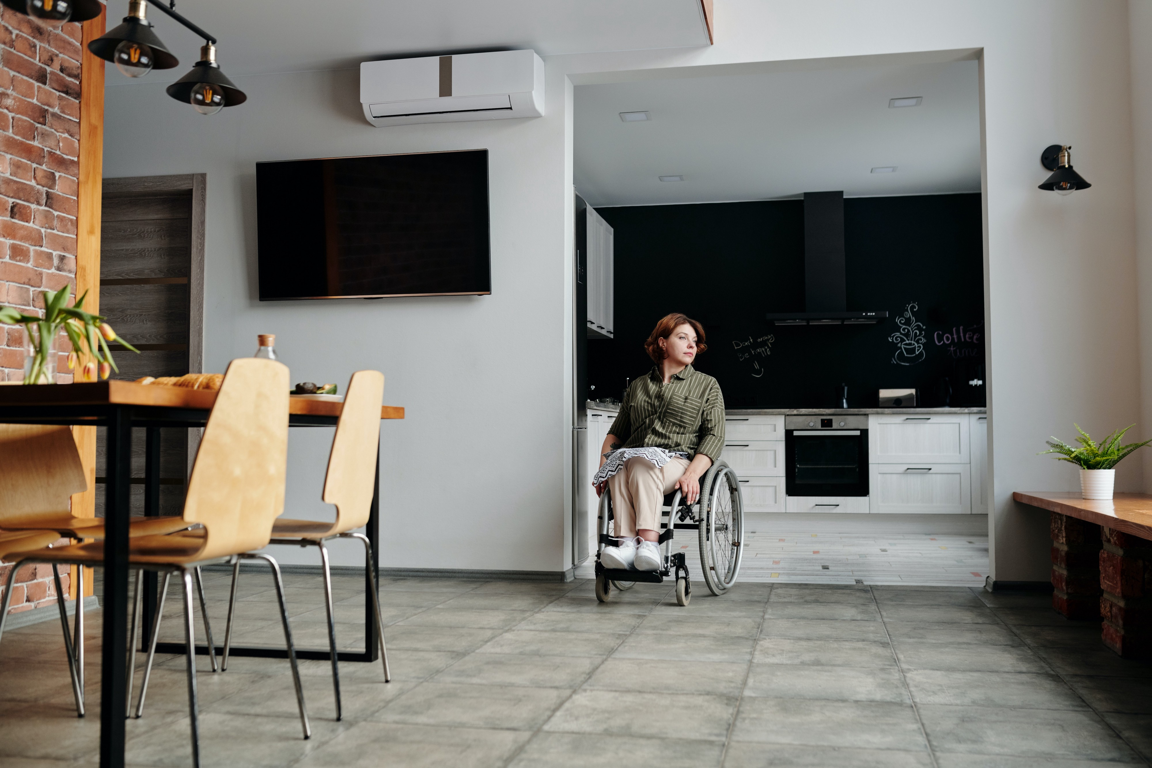 A woman in a wheelchair alone in her house