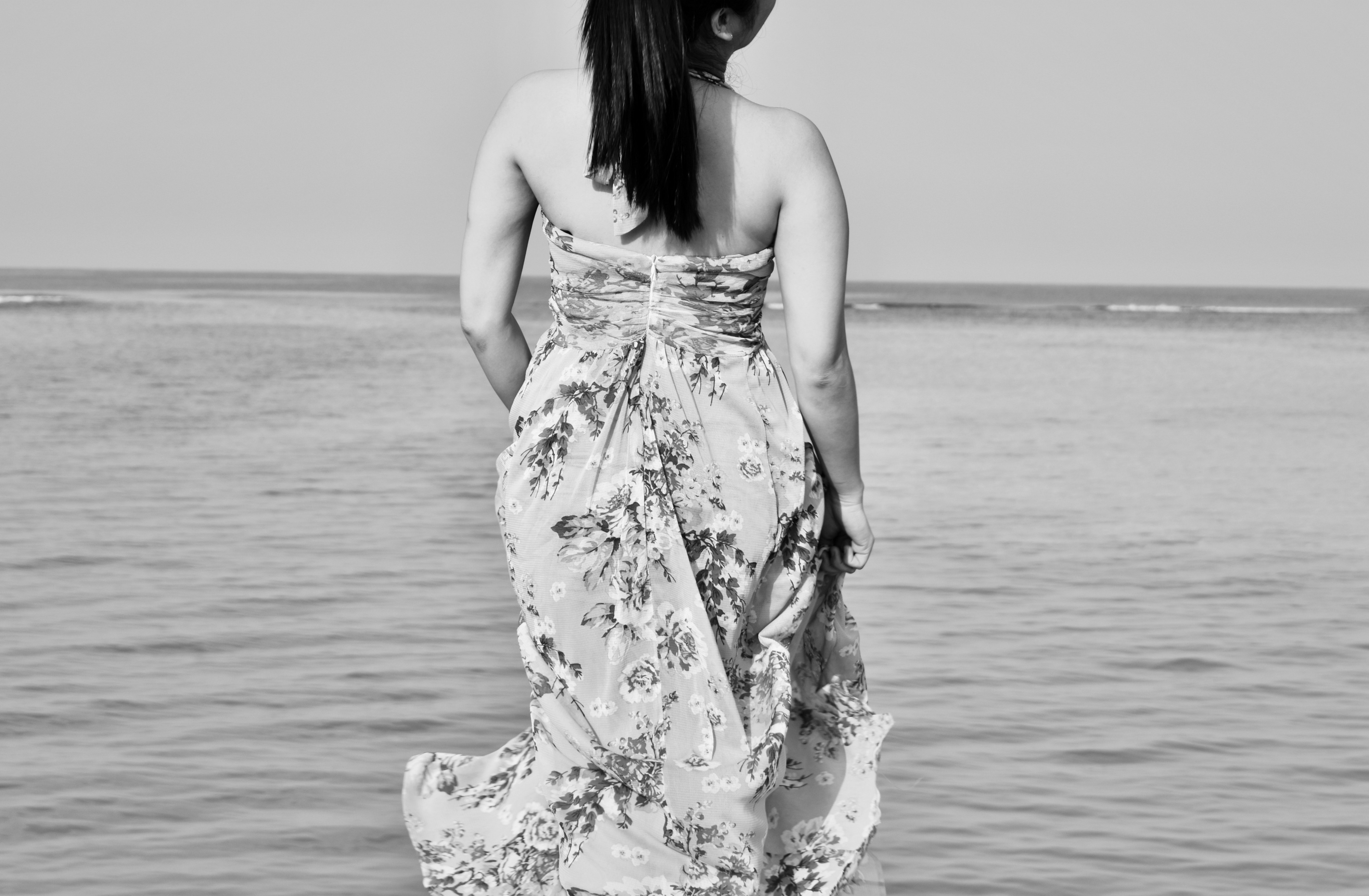 Back shot of a woman in dress floating above the sea