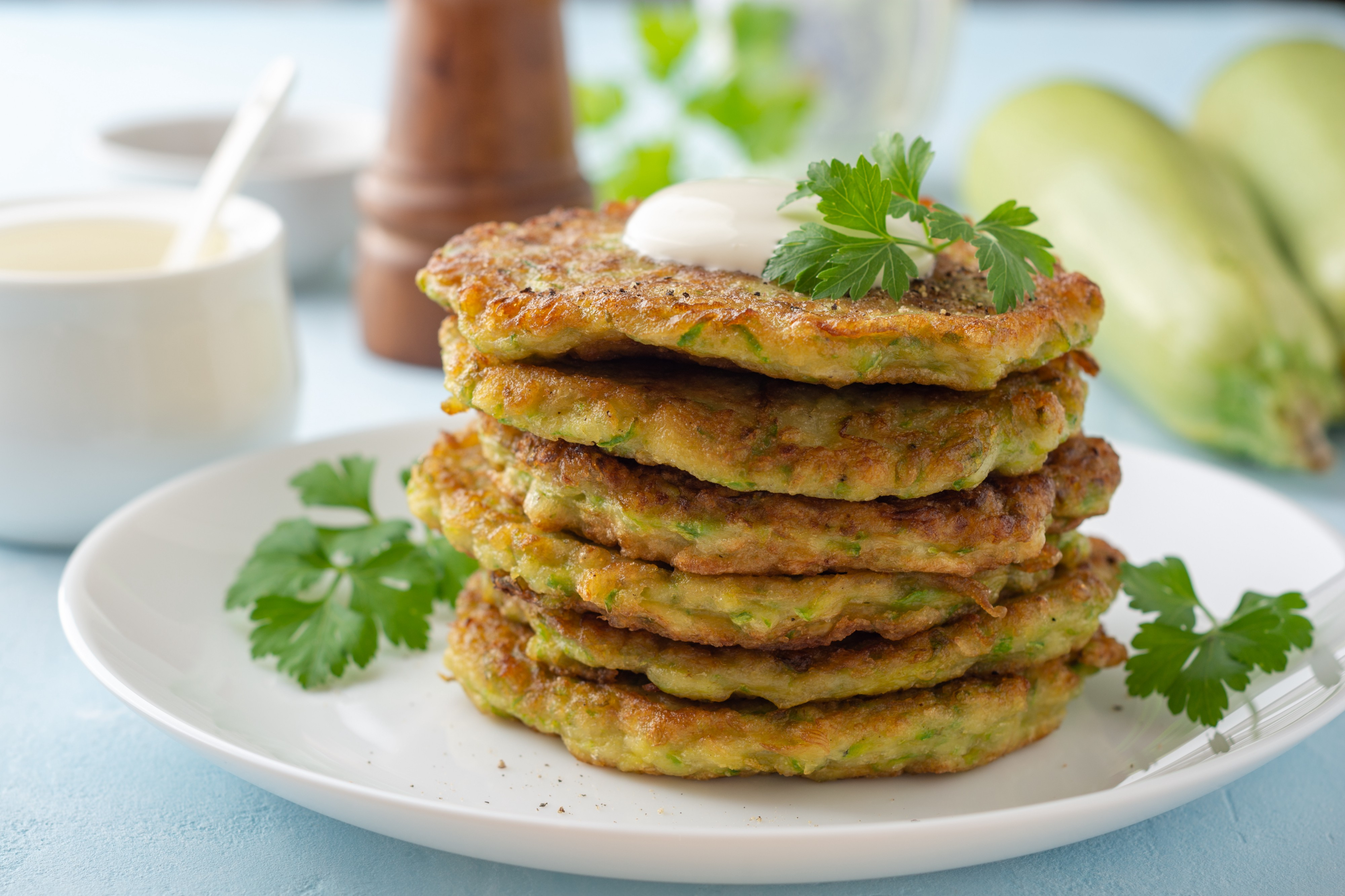 Zucchini fritters with fresh parsley and sour cream on a plate on a blue concrete background.