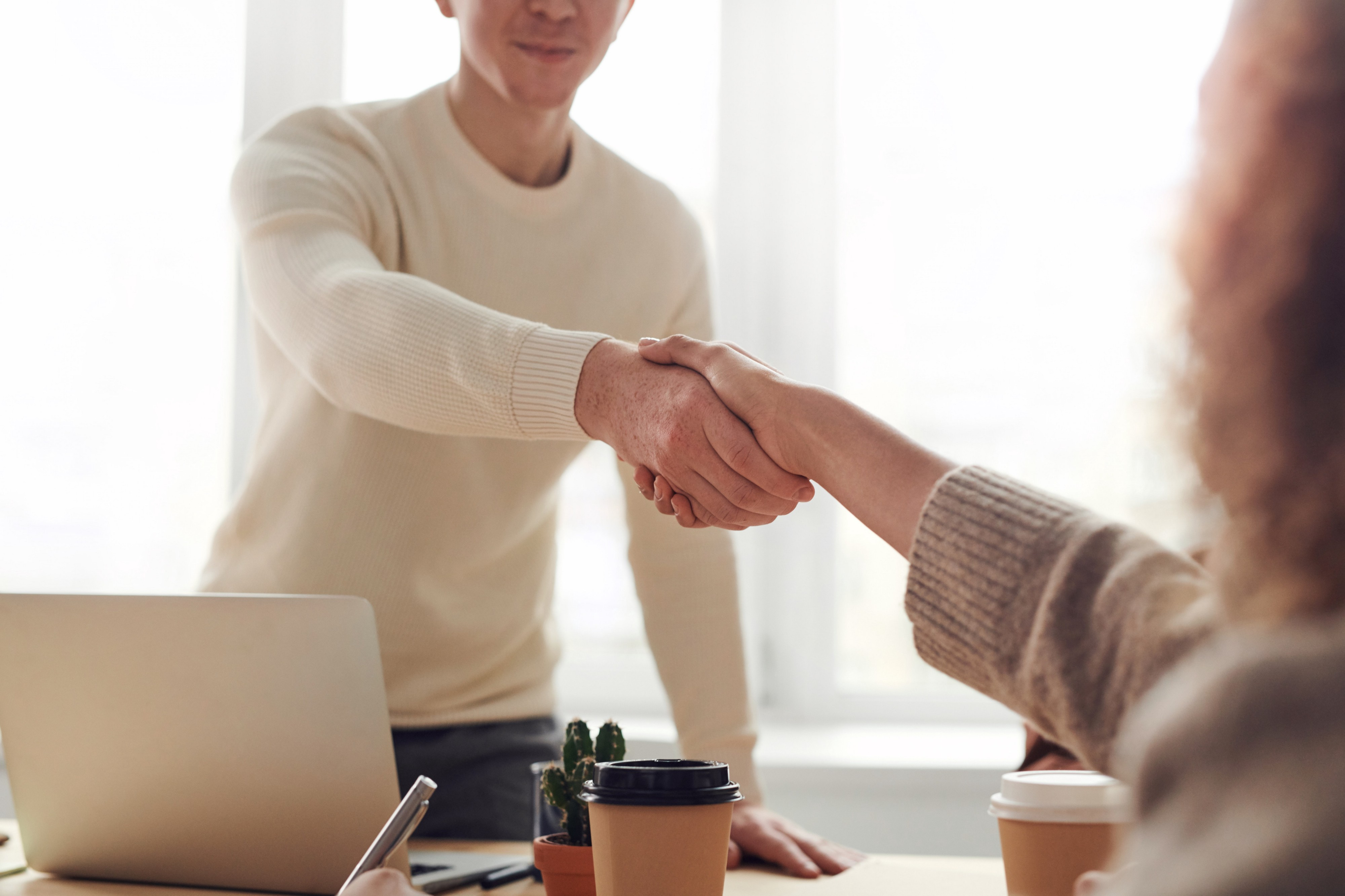 Men and woman shaking hands across a table in an office setting.