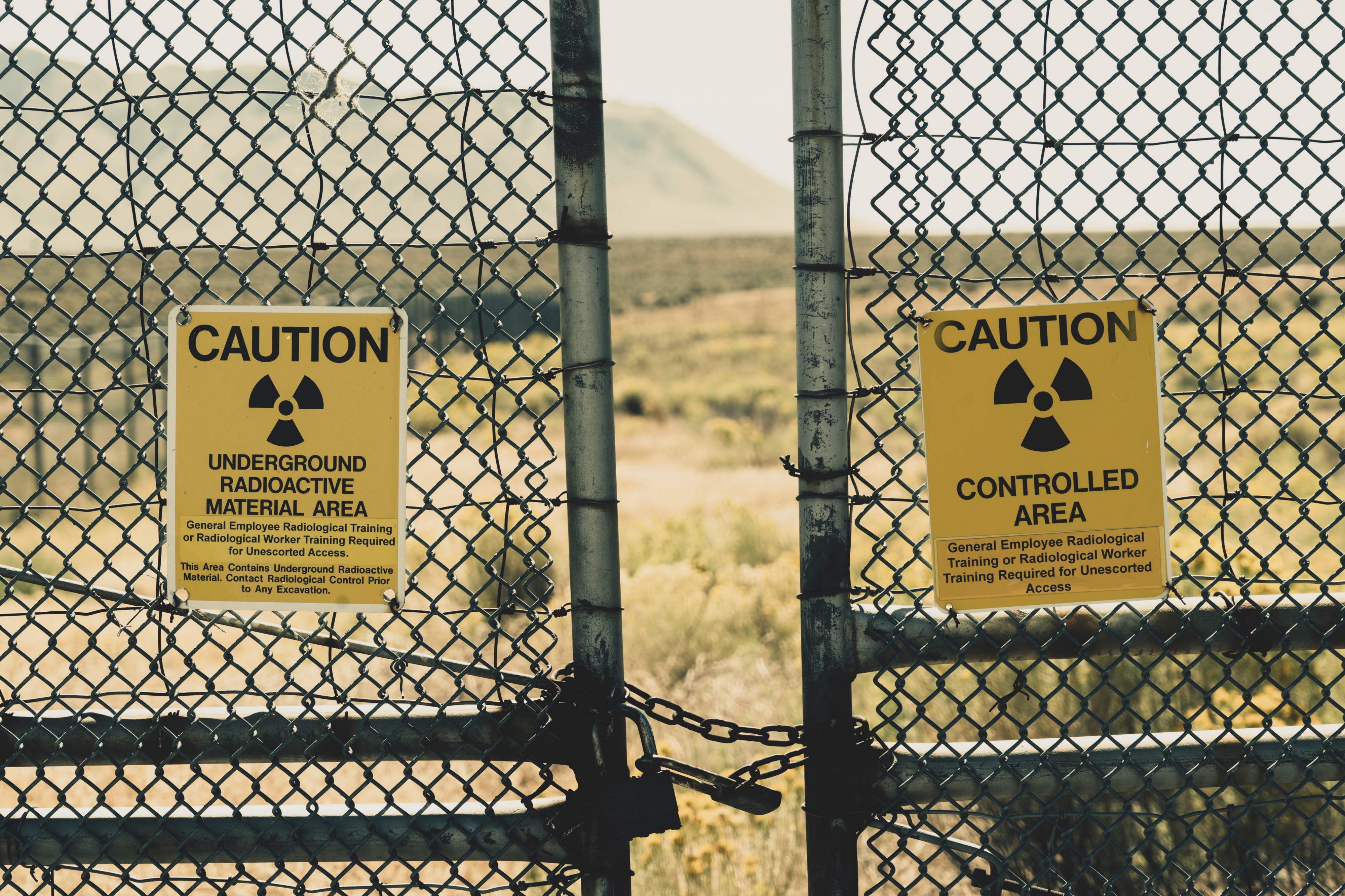 Chain link fence with yellow caution signs working about radioactivity