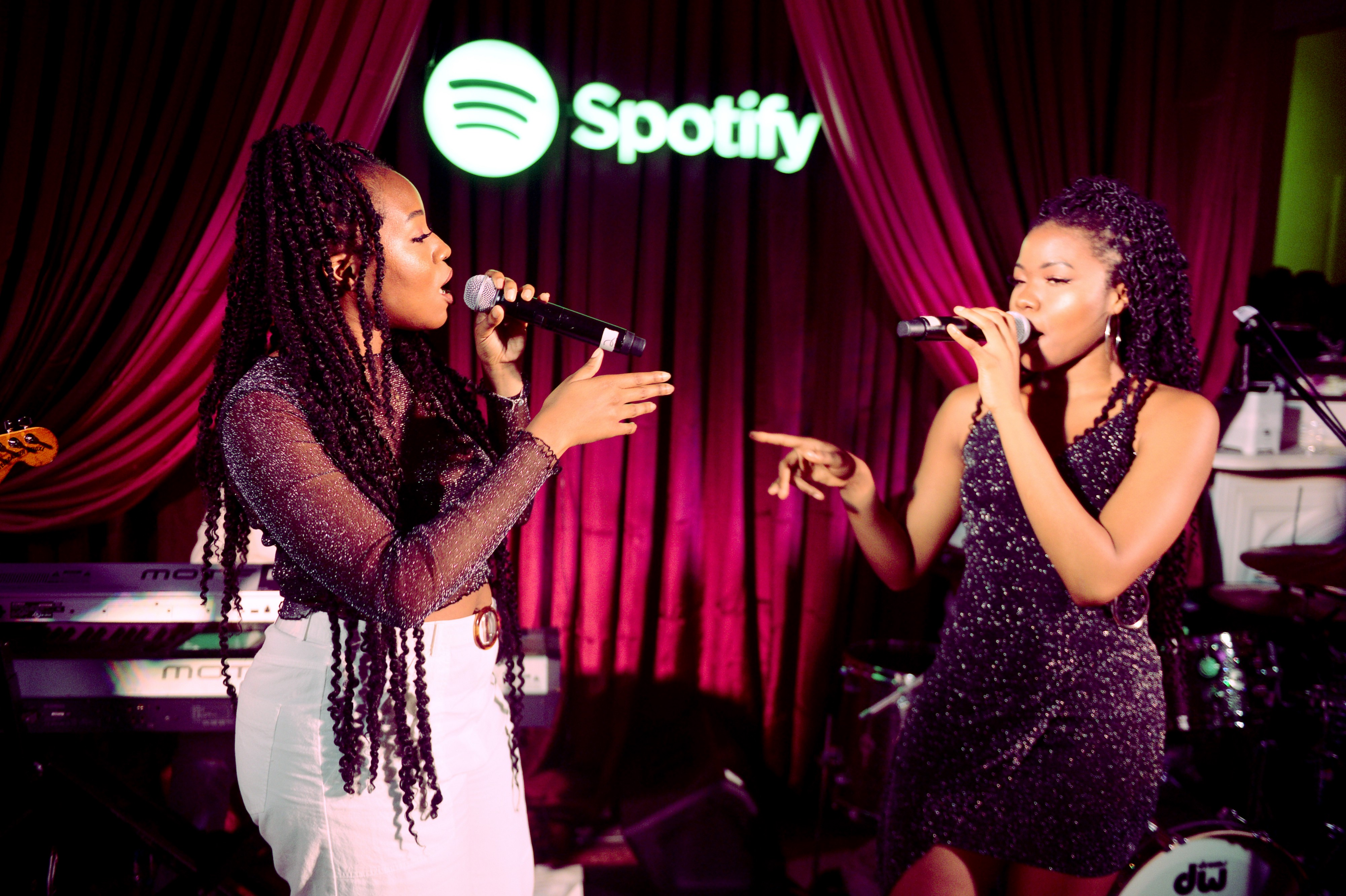 VanJess performing with mood lighting live with a Spotify logo in neon at the back. They are singing into their microphones and gesturing at each other.