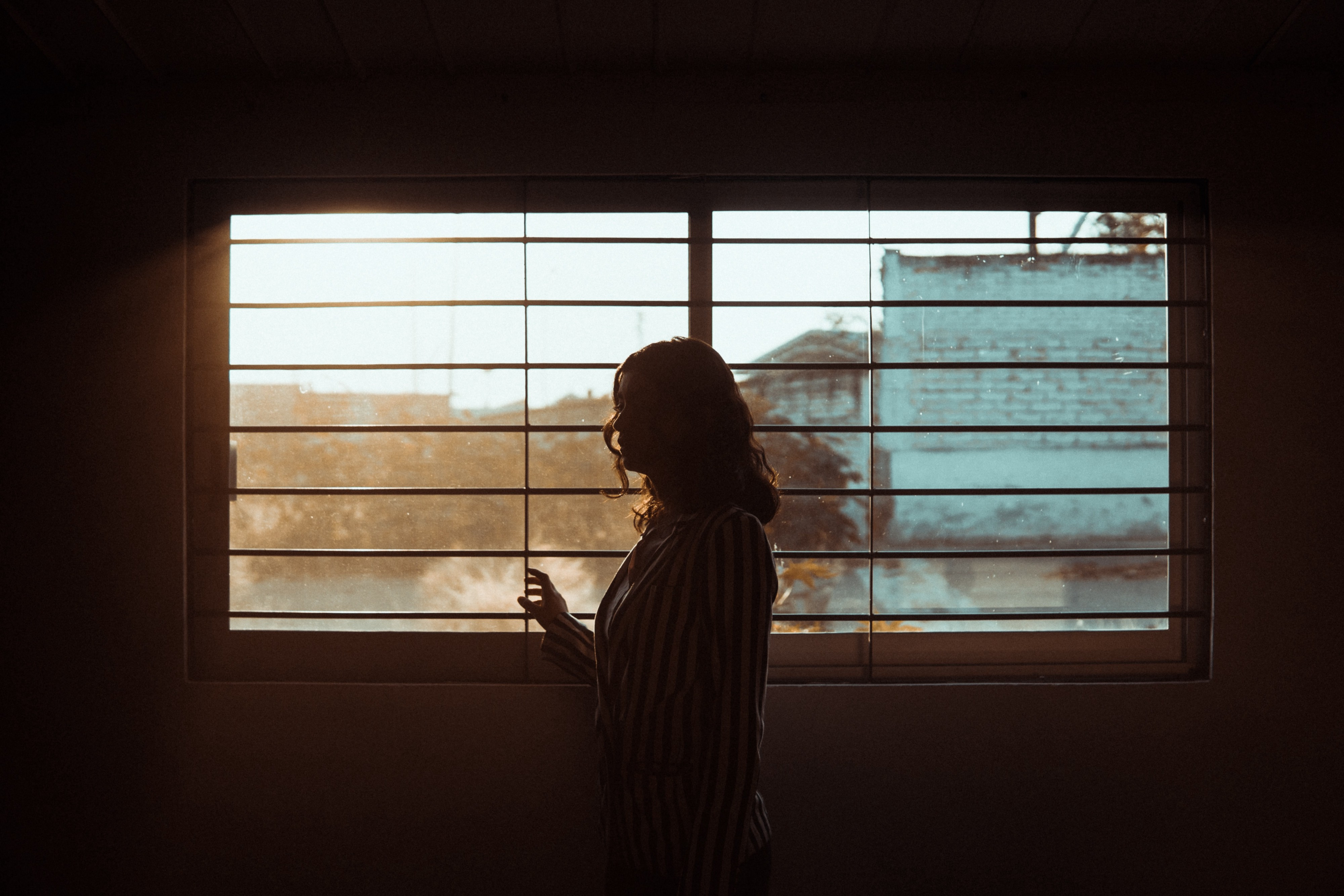 A woman's silhouette in front of a window.