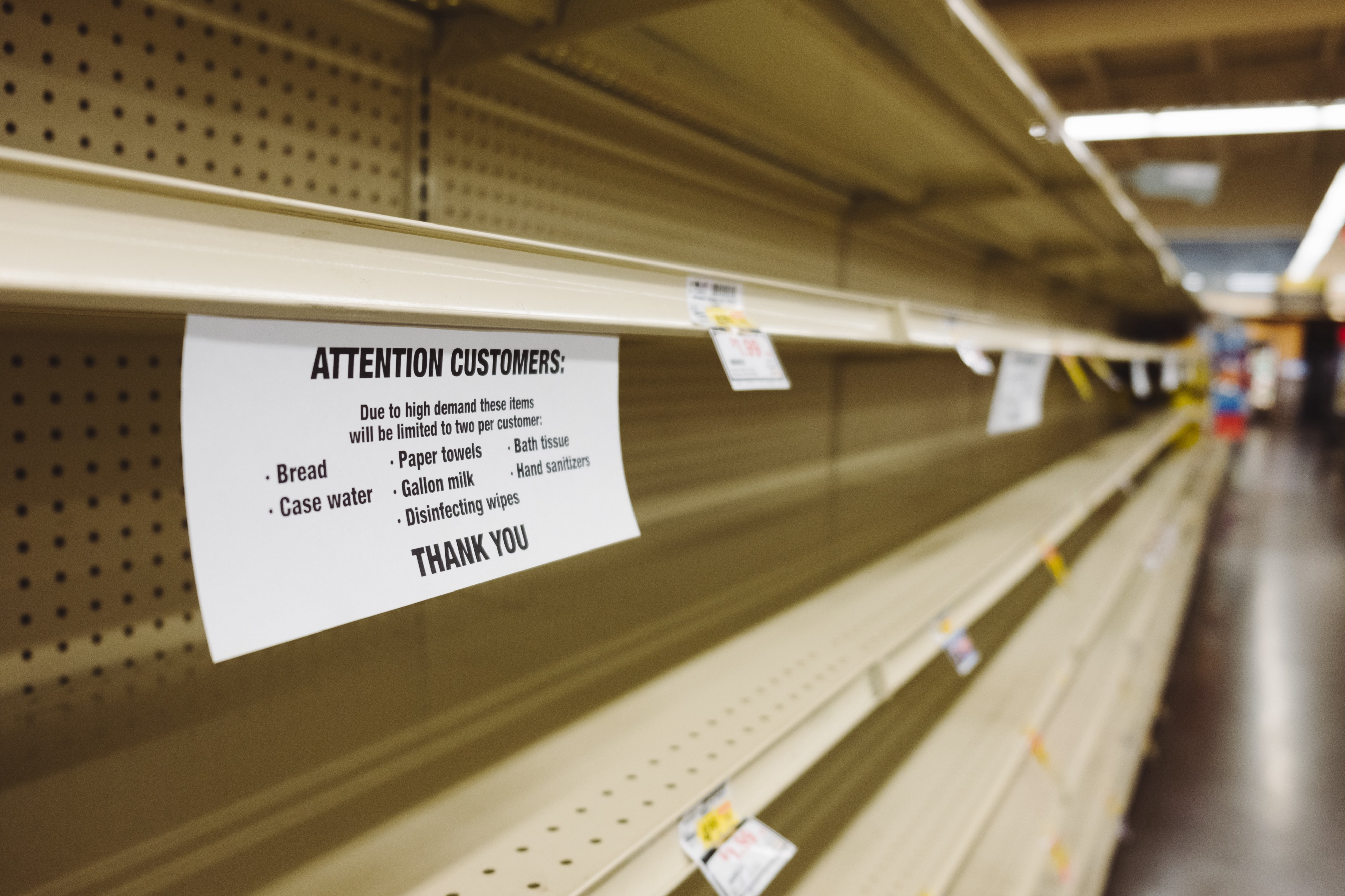 Empty grocery store shelves with sign says water, paper towels, tissues, disinfectant, sanitizer & other items are limited.