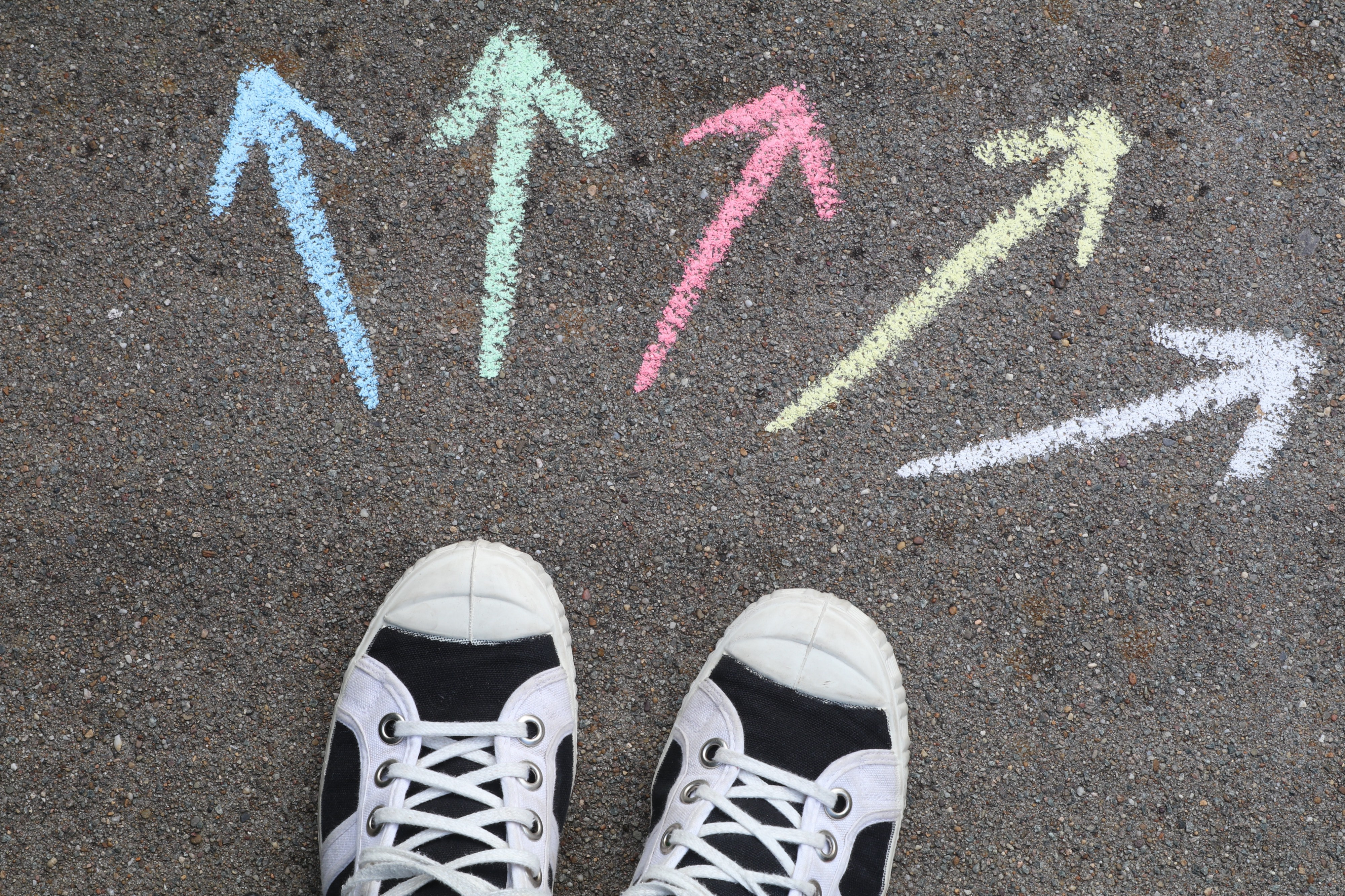 Which way do you go? Arrows pointing 5 different directions in front of sneakers.