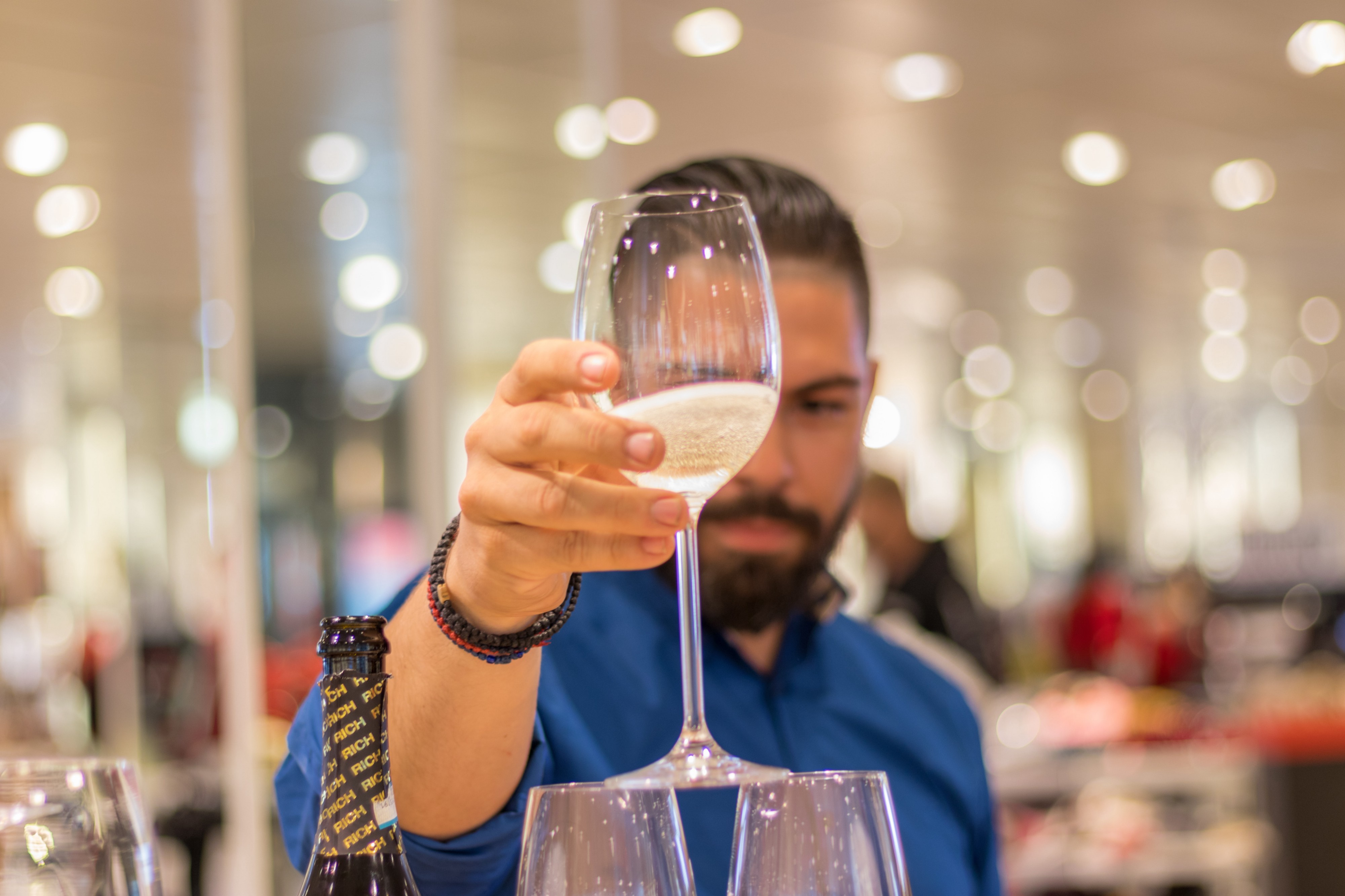 man balancing a wine glass on top of two other wine glasses