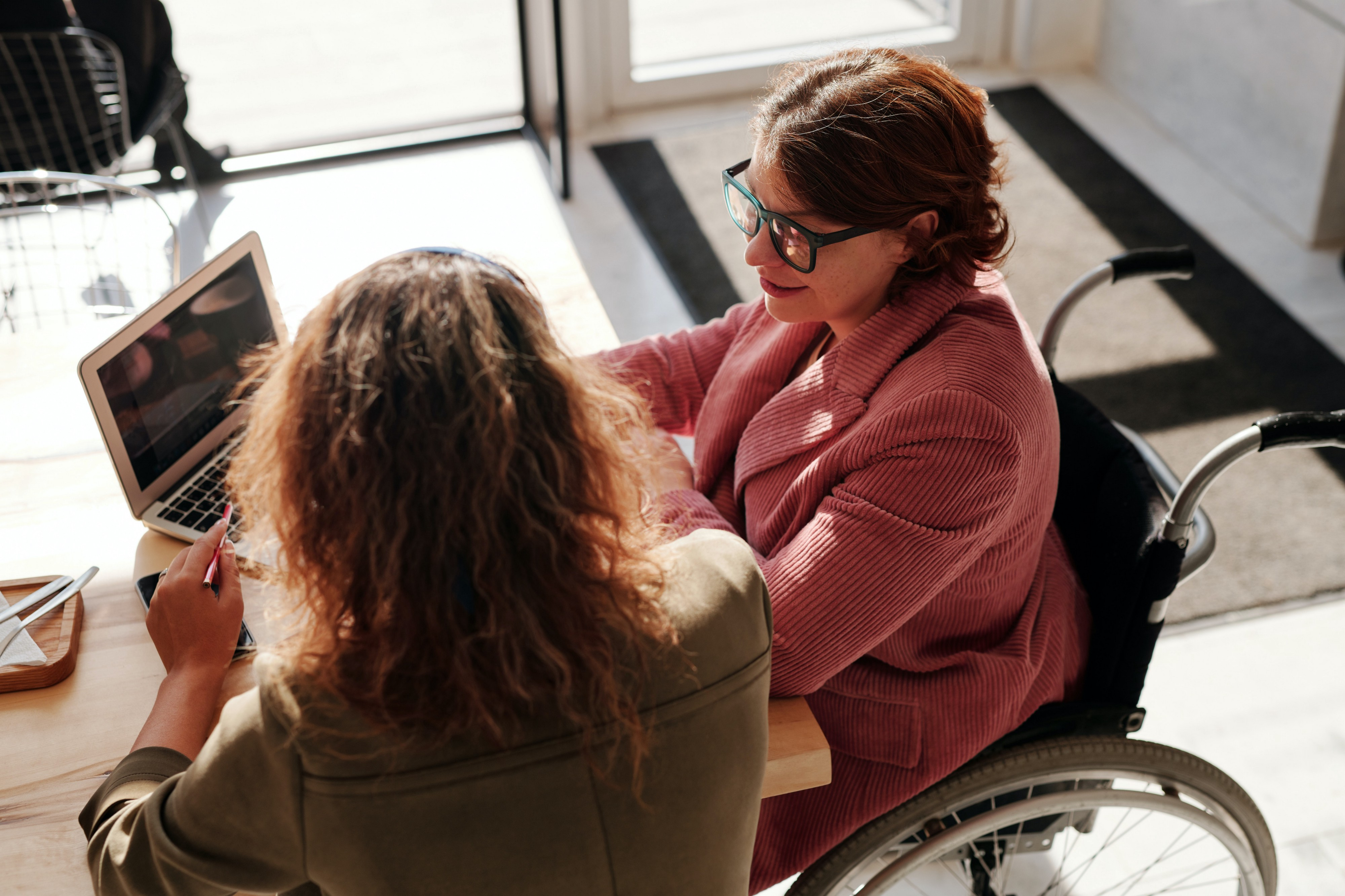 Two women having a conversation over a laptop. One of them is in a wheelchair.